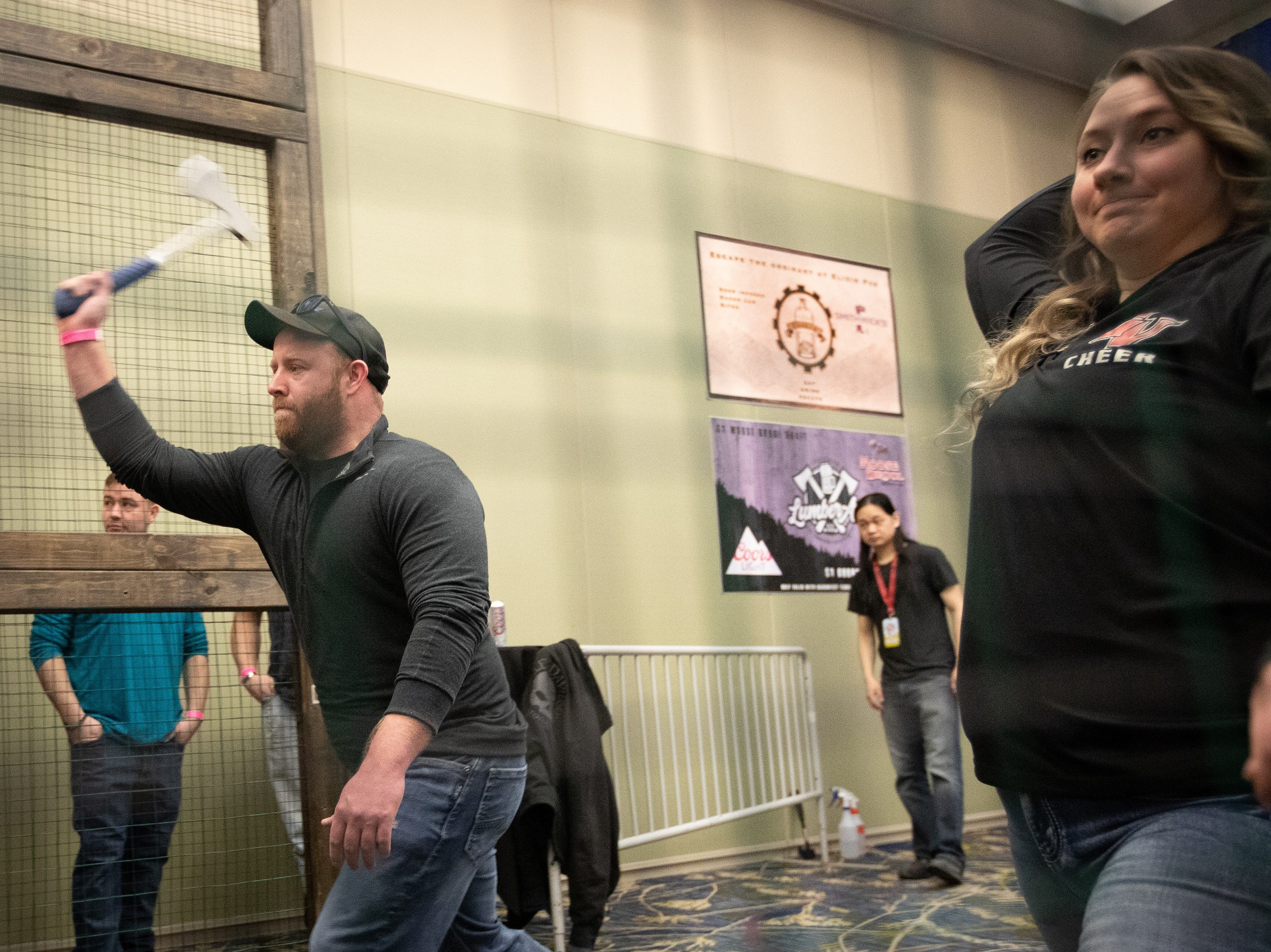 Aaron Brady and Nicole Thys, of Des Moines, throw axes during the Bacon Fest at Hy-Vee Hall on Feb. 16, 2019 in Des Moines, Iowa.