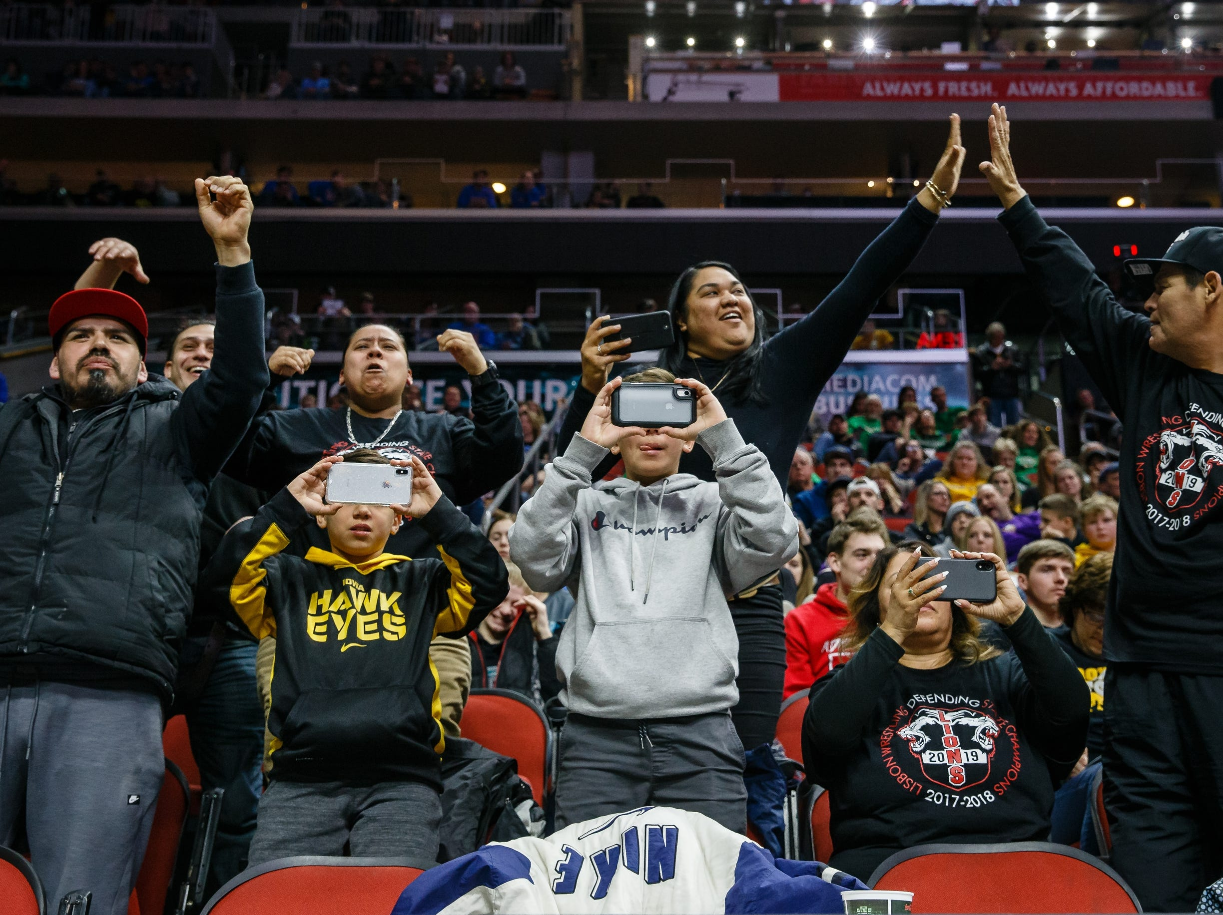 Fans cheer on their wrestlers during the class 1A 132 pound state championship semi-final match on Friday, Feb. 15, 2019 in Des Moines.