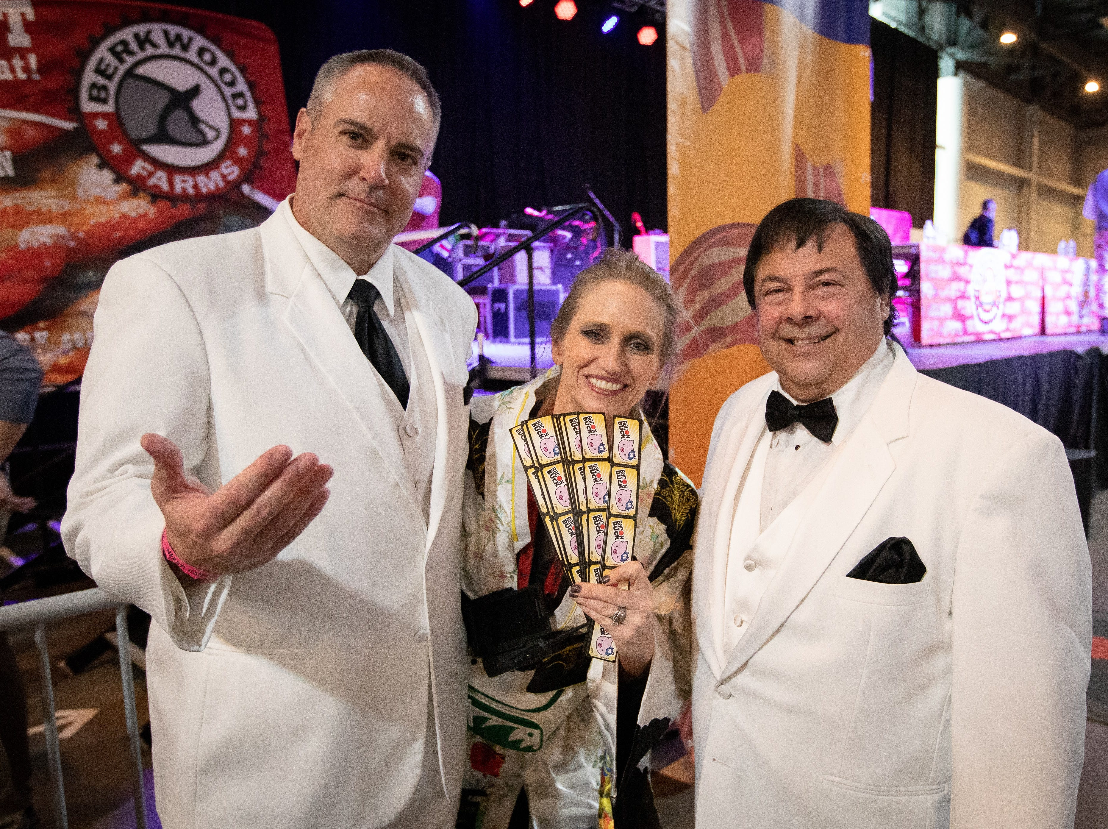 Paul Schulte, of Urbandale, and Davit Hott, of Des Moines, pose for a photo with Mindy Toyne, Festival Director, after winning the costume contest as characters from the tv show Fantasy Island during the Bacon Fest at Hy-Vee Hall on Feb. 16, 2019 in Des Moines, Iowa.