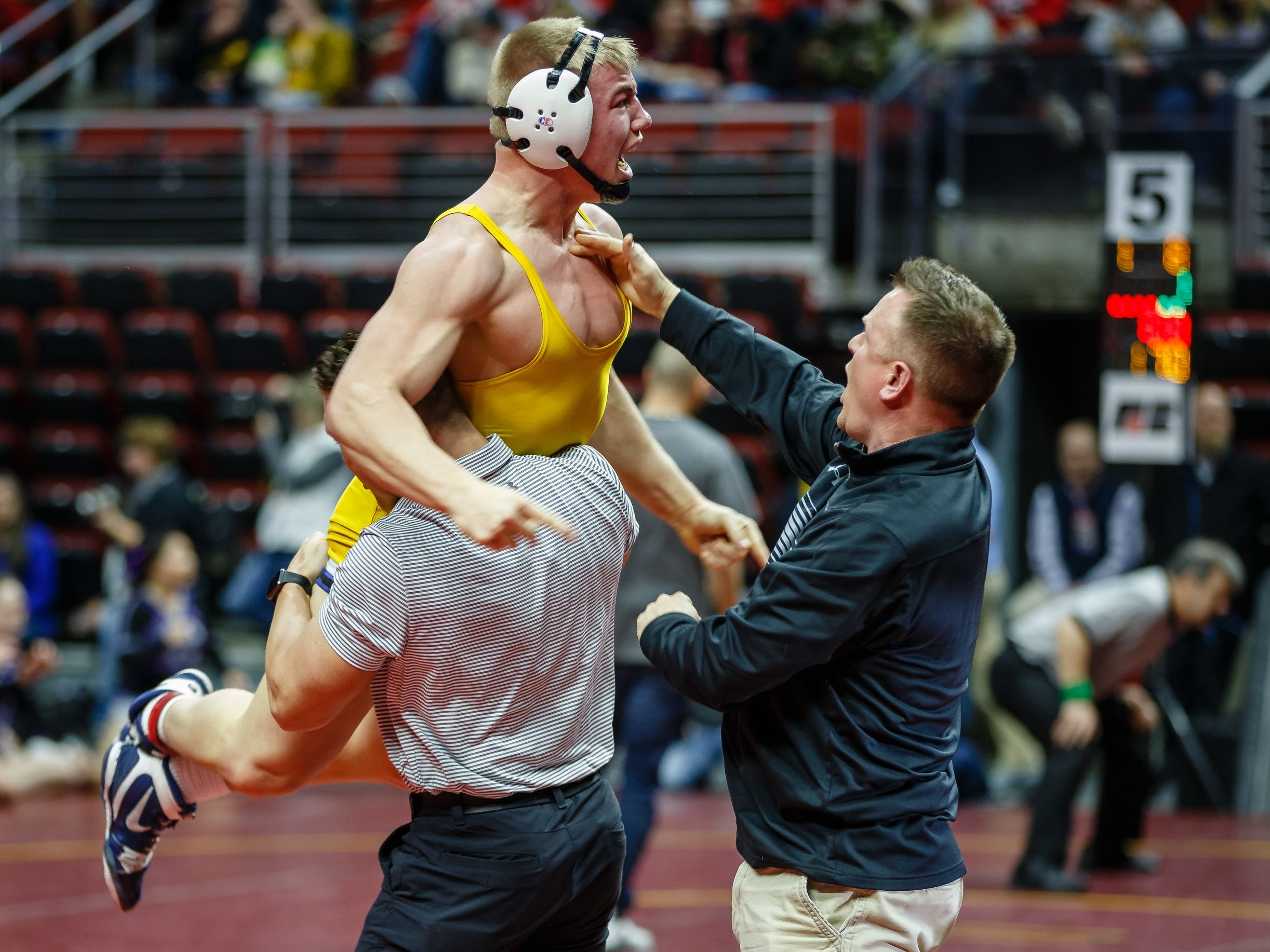 Thomas Even of Don Bosco jumps into his coaches arms after pinning Belmont Klemme's Tucker Kroeze during their class 1A 182 pound state championship semifinal match on Friday in Des Moines.