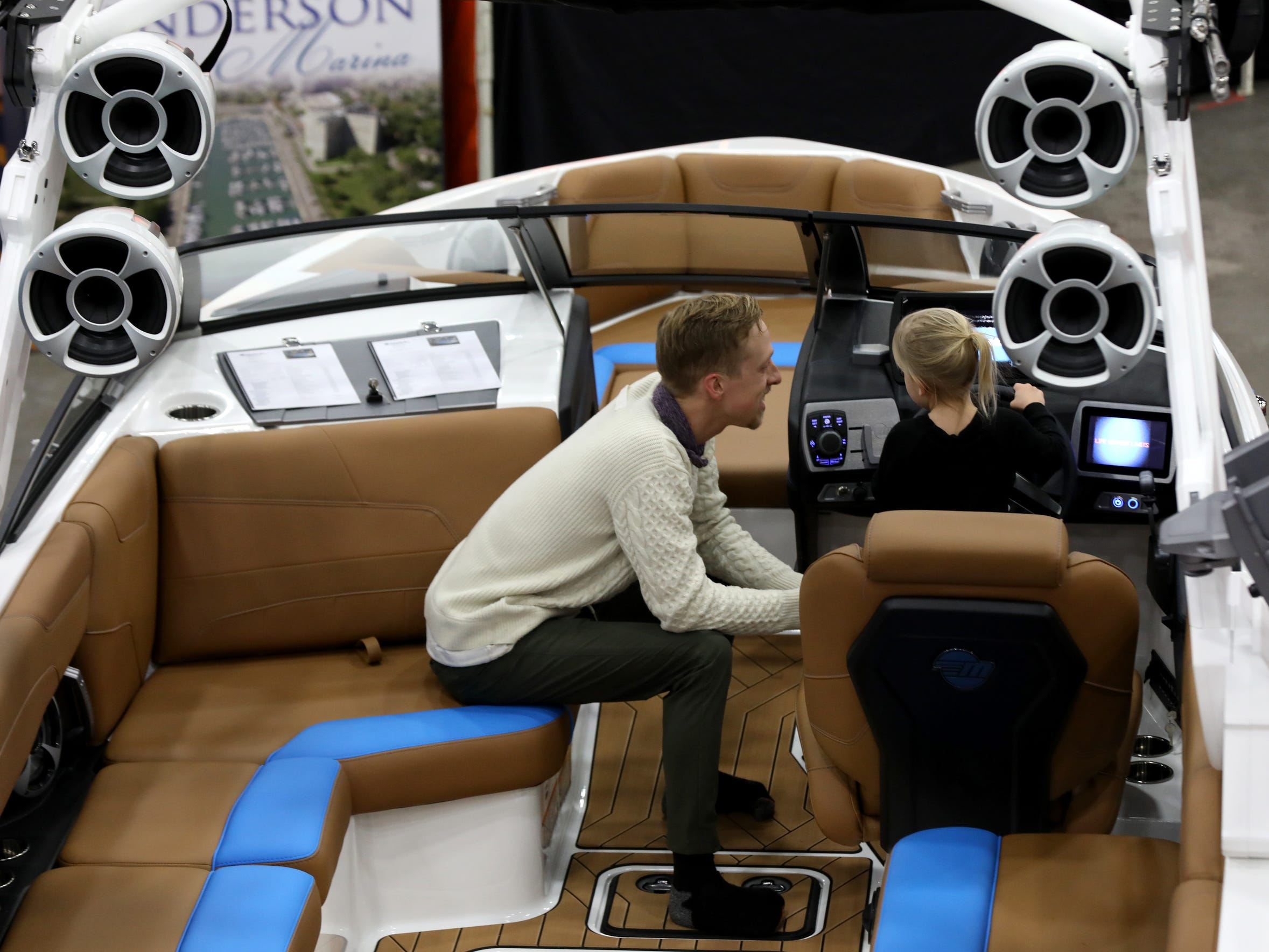 Brad Augustine, 30 of Grosse Pointe watching his daughter Isabella Augustine, 3 play around with the steering wheel on this Malibu boat at the Tommy's of Detroit display during the Detroit Boat Show at Cobo Center in Detroit on Saturday, February 16, 2019..