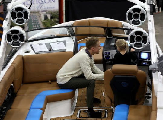 Brad Augustine, 30 of Grosse Pointe watching his daughter Isabella Augustine, 3 play around with the steering wheel on this Malibu boat at the Tommy's of Detroit display during the Detroit Boat Show at Cobo Center in Detroit on Saturday, February 16, 2019.