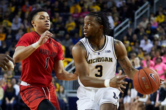 Zavier Simpson is defended by Maryland's Anthony Cowan Jr. in the first half Saturday at Crisler Center.
