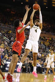 Isaiah Livers shoots over Maryland's Ricky Lindo Jr. at Crisler Center on Saturday in Ann Arbor.