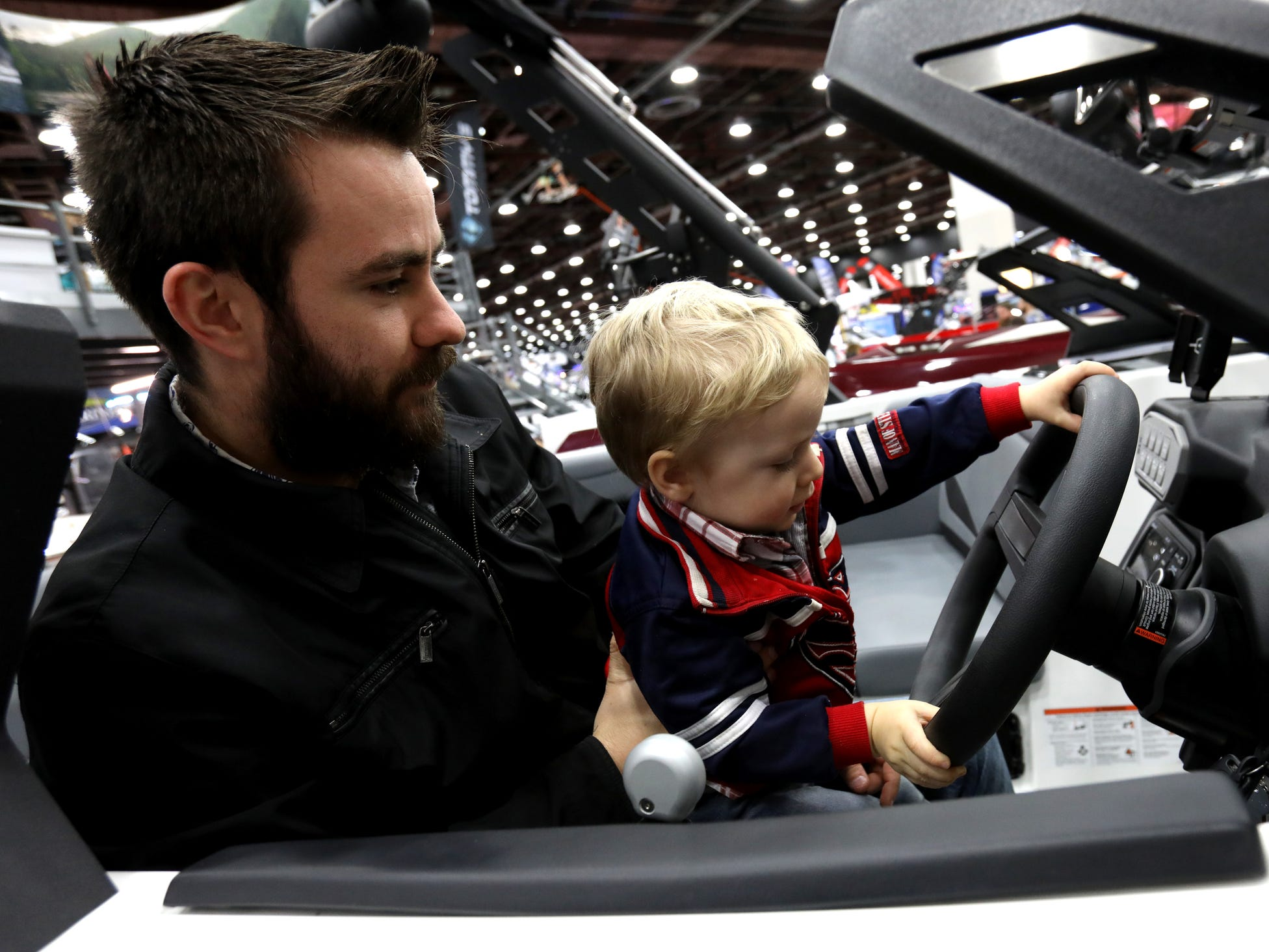 Sam Eis, 26 of Prescott, Ariz., watches his son Jadon Eis, 2 play with a boat at the Tommy's of Detroit display during the Detroit Boat Show at Cobo Center in Detroit on Saturday, February 16, 2019.     .