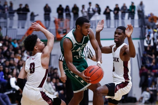 Detroit Cass Tech's Tyson Acuff (11) tries to pass the ball as he's defended by Detroit Renaissance's Keon Henderson (0) and Kaylein Marzetter (5) during the first half of the PSL boys basketball championship game at Cass Tech High School in Detroit, Friday, Feb. 15, 2019.