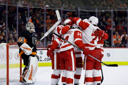 Detroit Red Wings 'Gustav Nyquist (14) celebrates with teammates after scoring fits Philadelphia Flyers' Carter Hart during the first period Saturday, Feb. 16, 2019, in Philadelphia