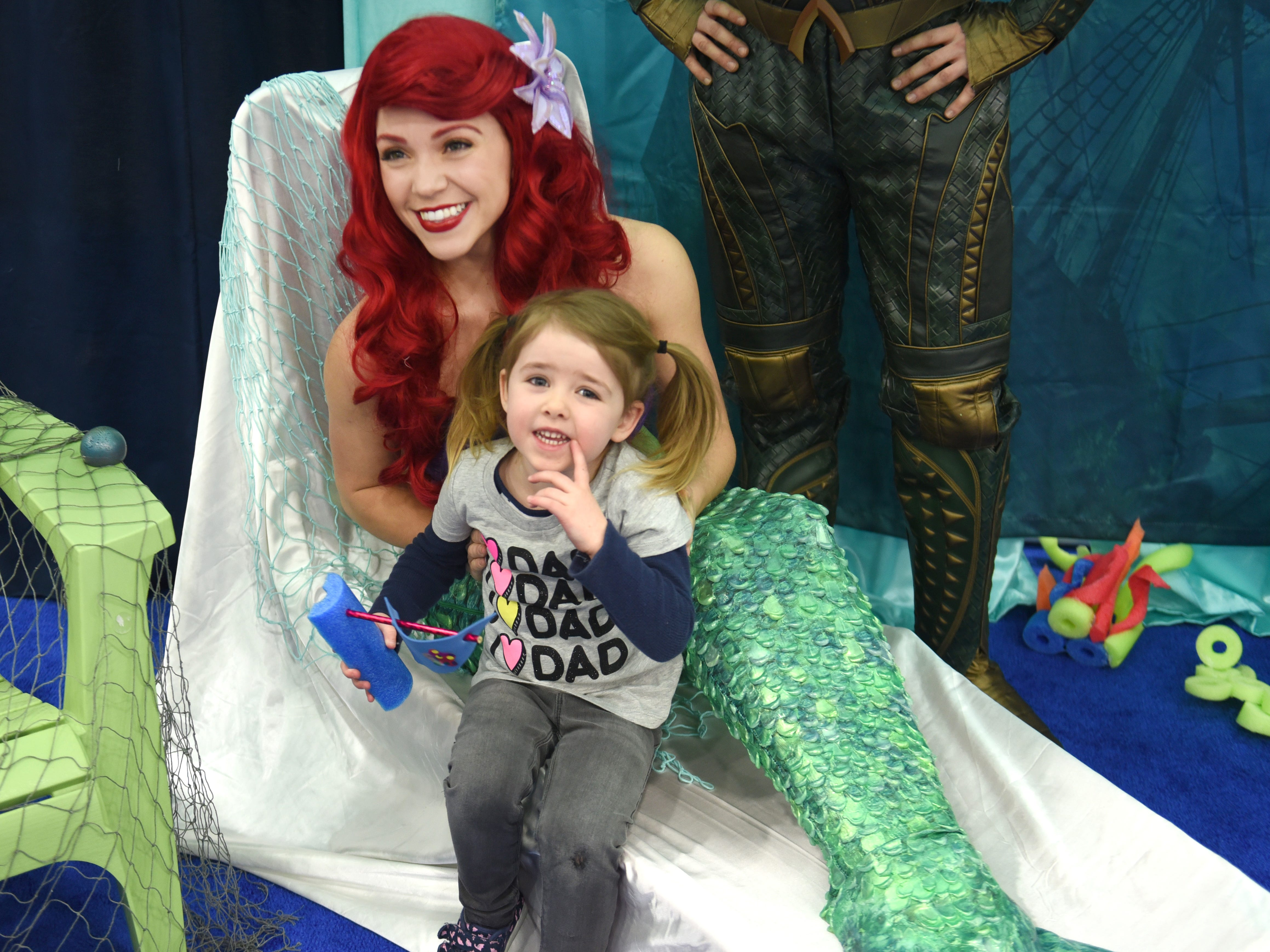 Sara Kmiec, of The Enchanted Princess Party, Madison Heights, wears a mermaid costume and takes a photograph with Vivian Borck at the Detroit Boat Show at Cobo Center on Saturday, February 16, 2018.