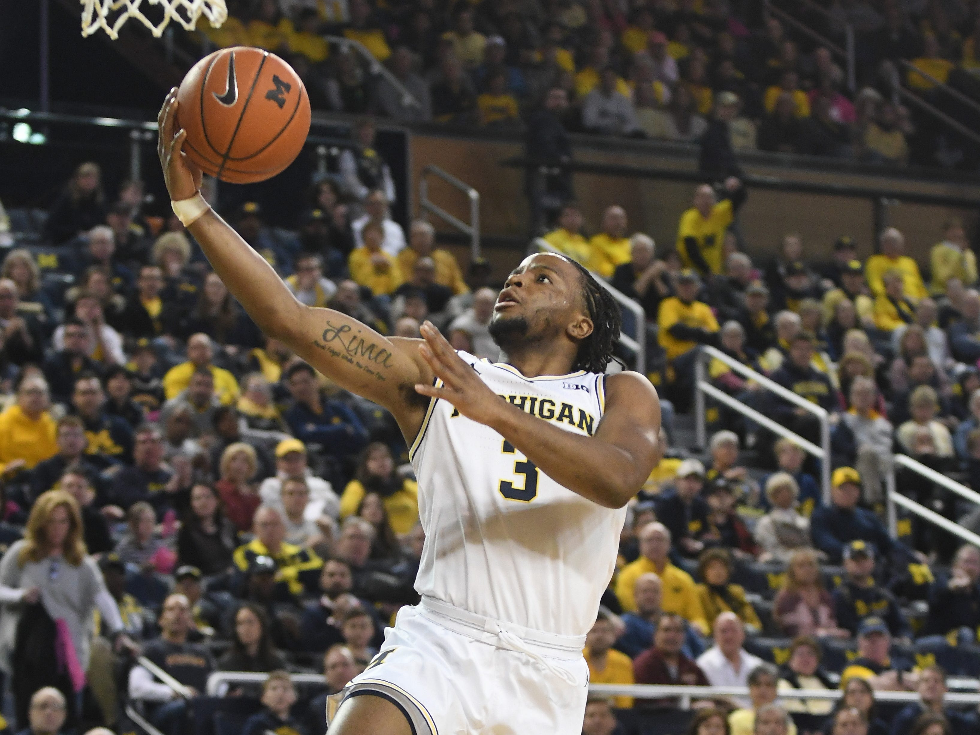 Michigan's Zavier Simpson lays in two points on a fast break in the first half.