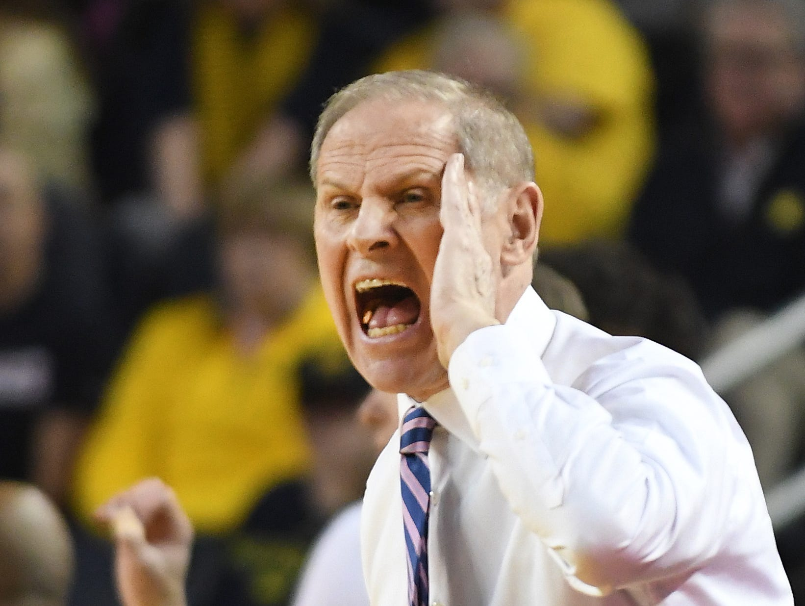 Michigan coach Jon Beilein calls out to his players on the court in the first half.