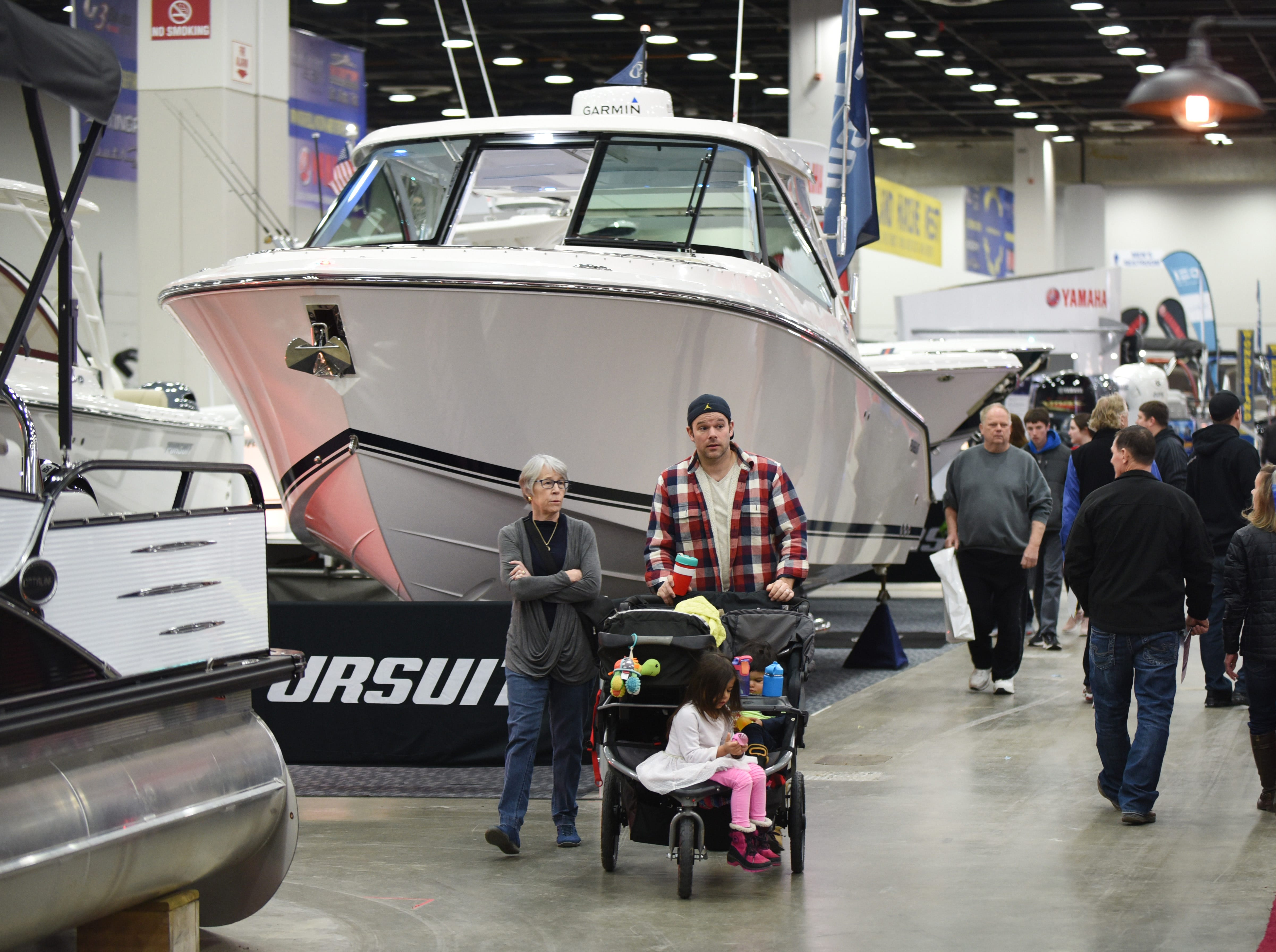 People walk passed a Pursuit DC 325 Dual Console boat from Lands End Marina, Harrison Township, at the Detroit Boat Show.