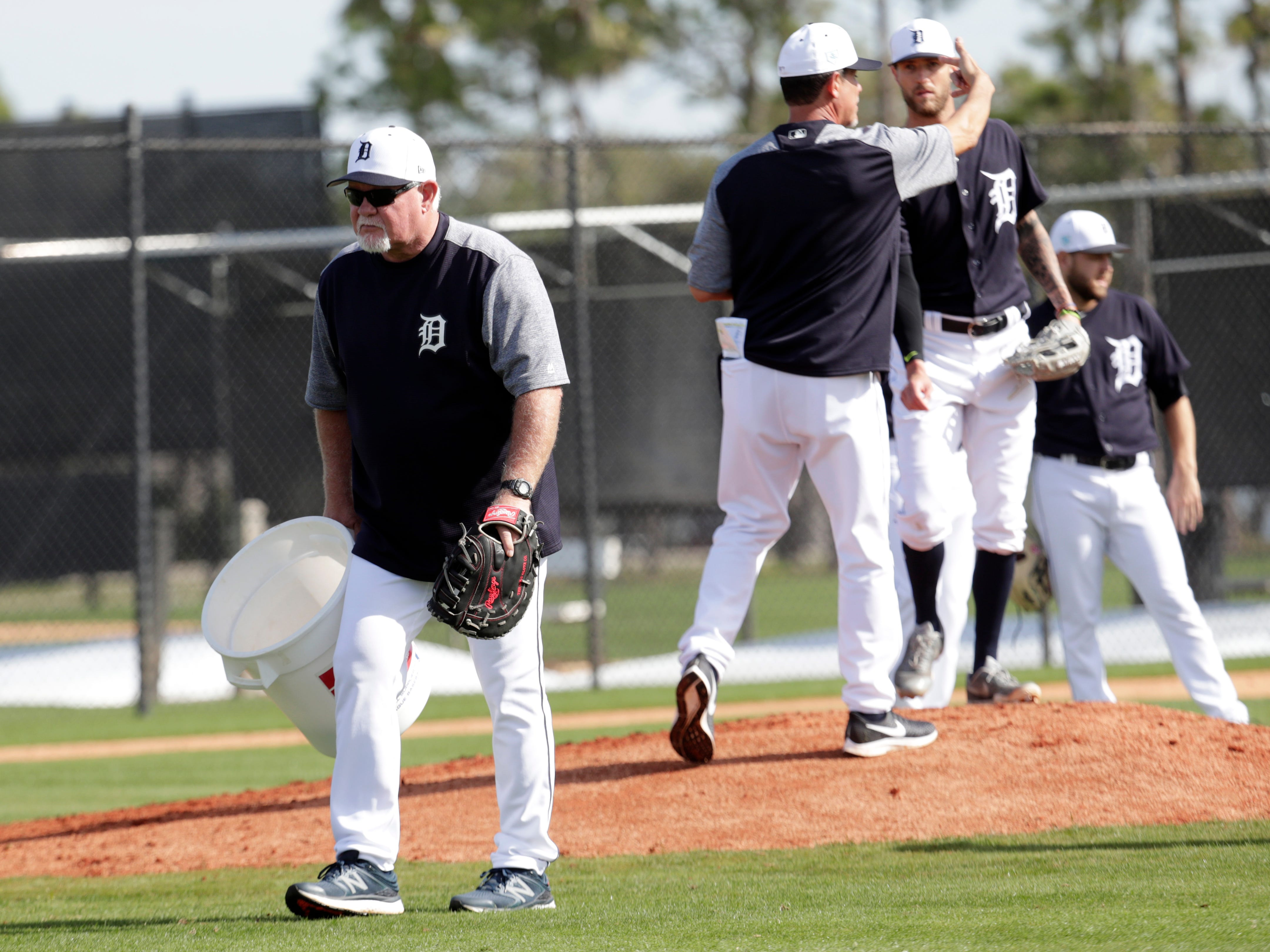 Detroit Tigers manager Ron Gardenhire collects balls as players do drills.