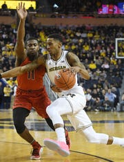 Michigan's Charles Matthews heads to the basket with Maryland's Darryl Morsell defending in the first half.