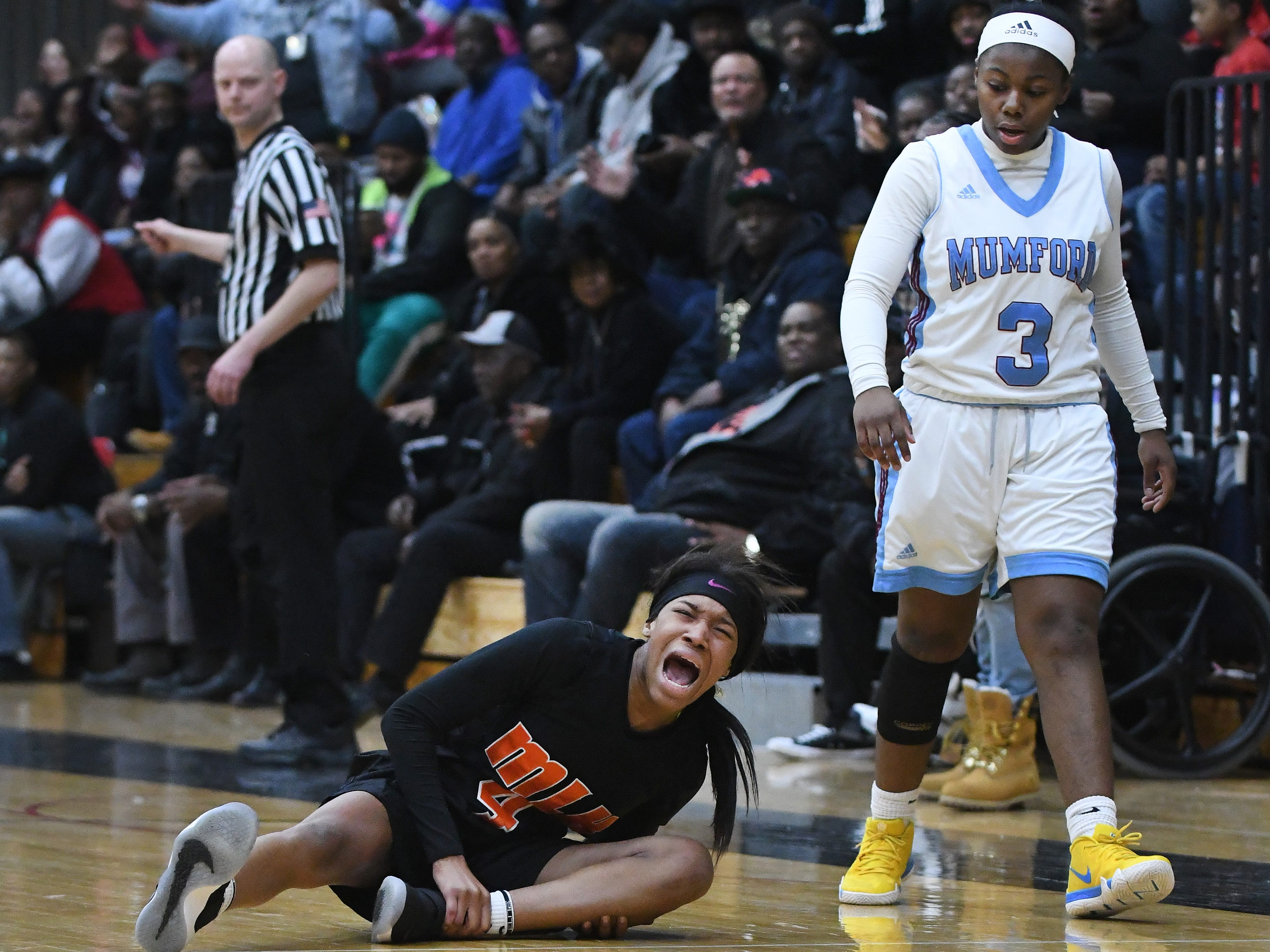 King's Del'Janae Williams twists her ankle on a hard foul as Mumford's Coreeahn Yharbrough walks past in the second half.