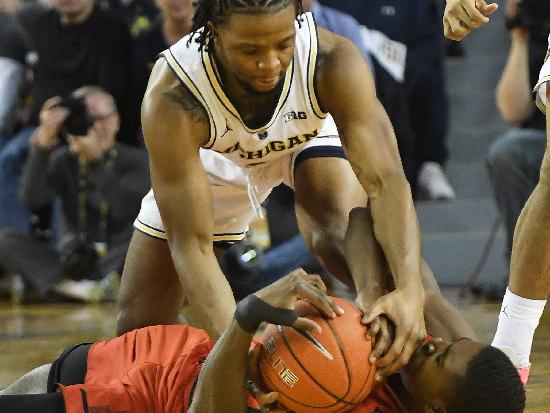 Michigan's Zavier Simpson and Maryland's Darryl Morsell battle for a loose ball in the first half.