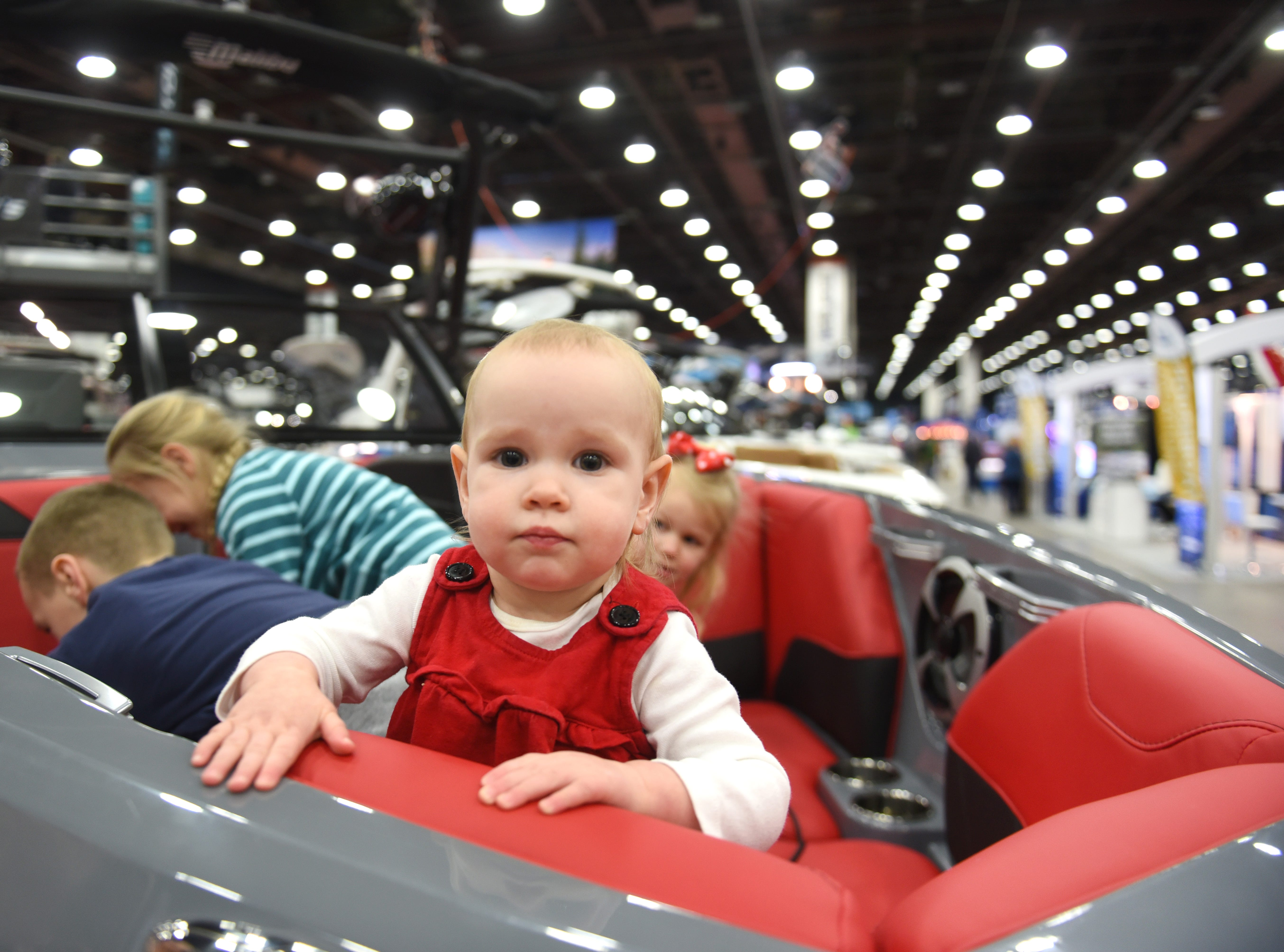 16-month-old Autumn Gehman, of Rochester, enjoys  the comfort of a 2019 Malibu 23 LSV from Tommy's of Detroit, Waterford, during the Detroit Boat Show at Cobo Center on Saturday, February 16, 2018.