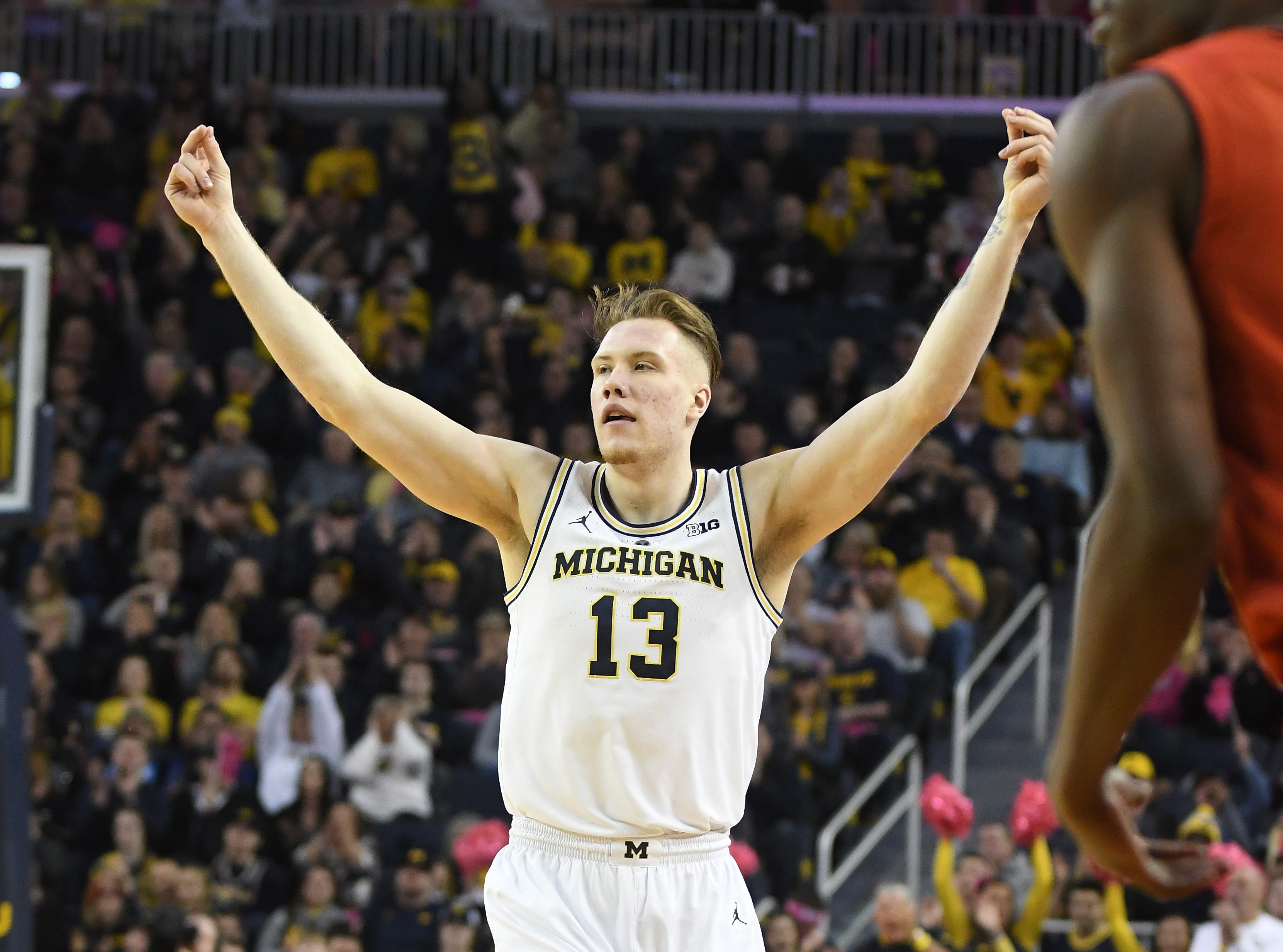 Michigan's Ignas Brazdeikis raises his arms after sinking a shot in the first half.
