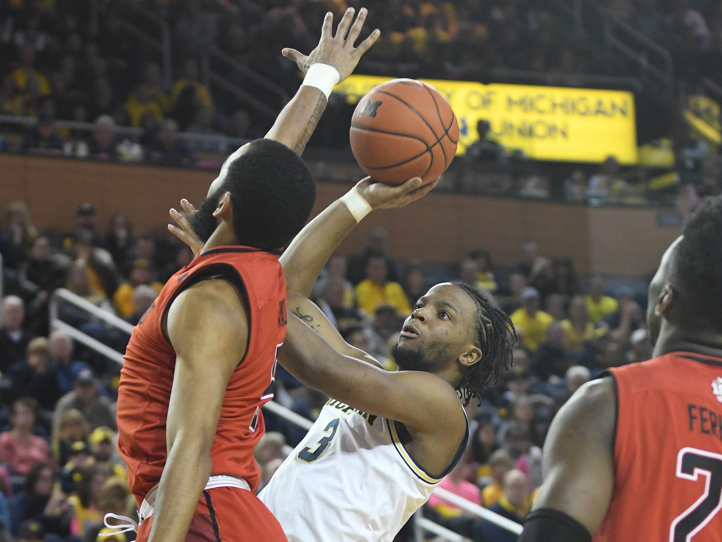Michigan's Zavier Simpson puts up a shot against Maryland's Anthony Cowan Jr. in the second half.
