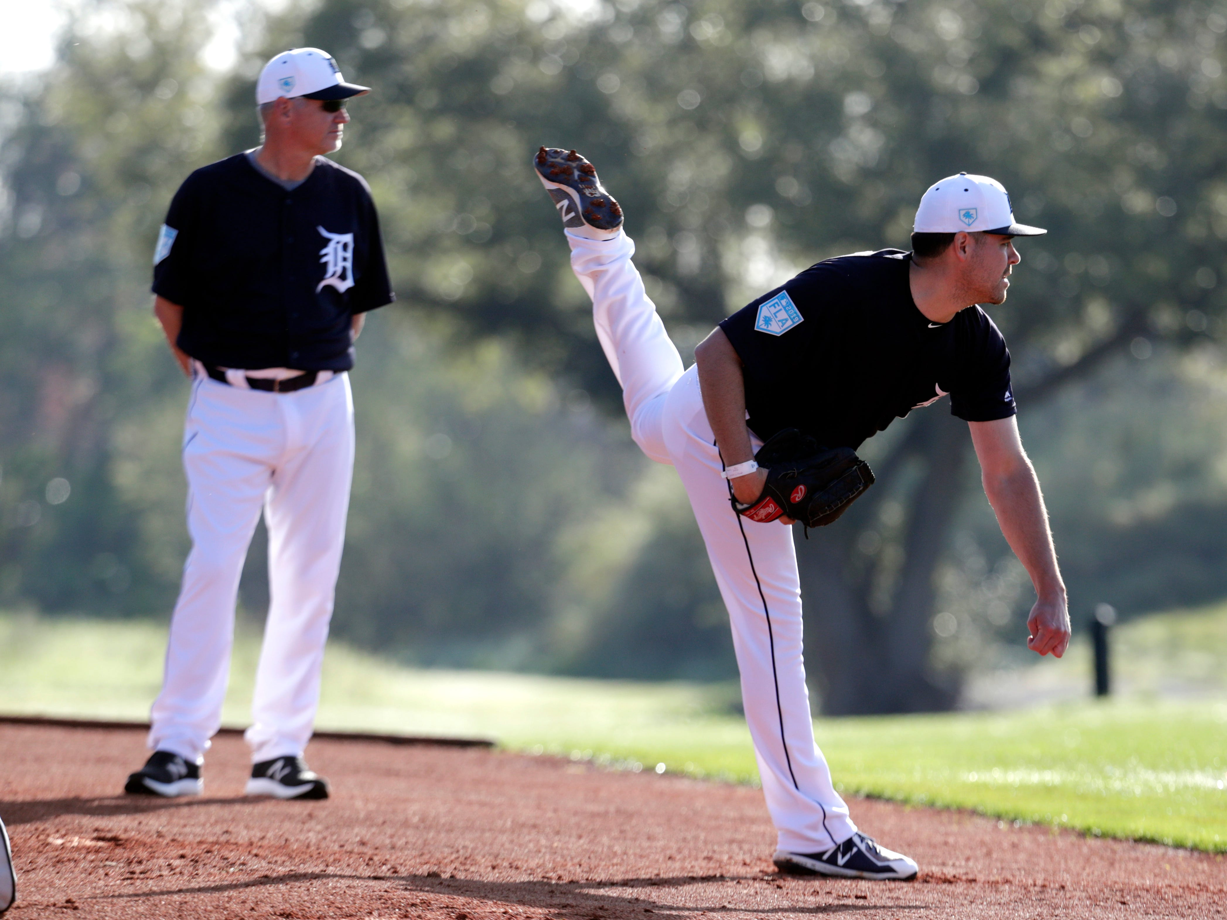 Detroit Tigers pitcher Matt Moore, right, follows through on a delivery as bullpen coach Jeff Pico looks on at the Detroit Tigers' spring training baseball facility, Friday, Feb. 15, 2019, in Lakeland, Fla.