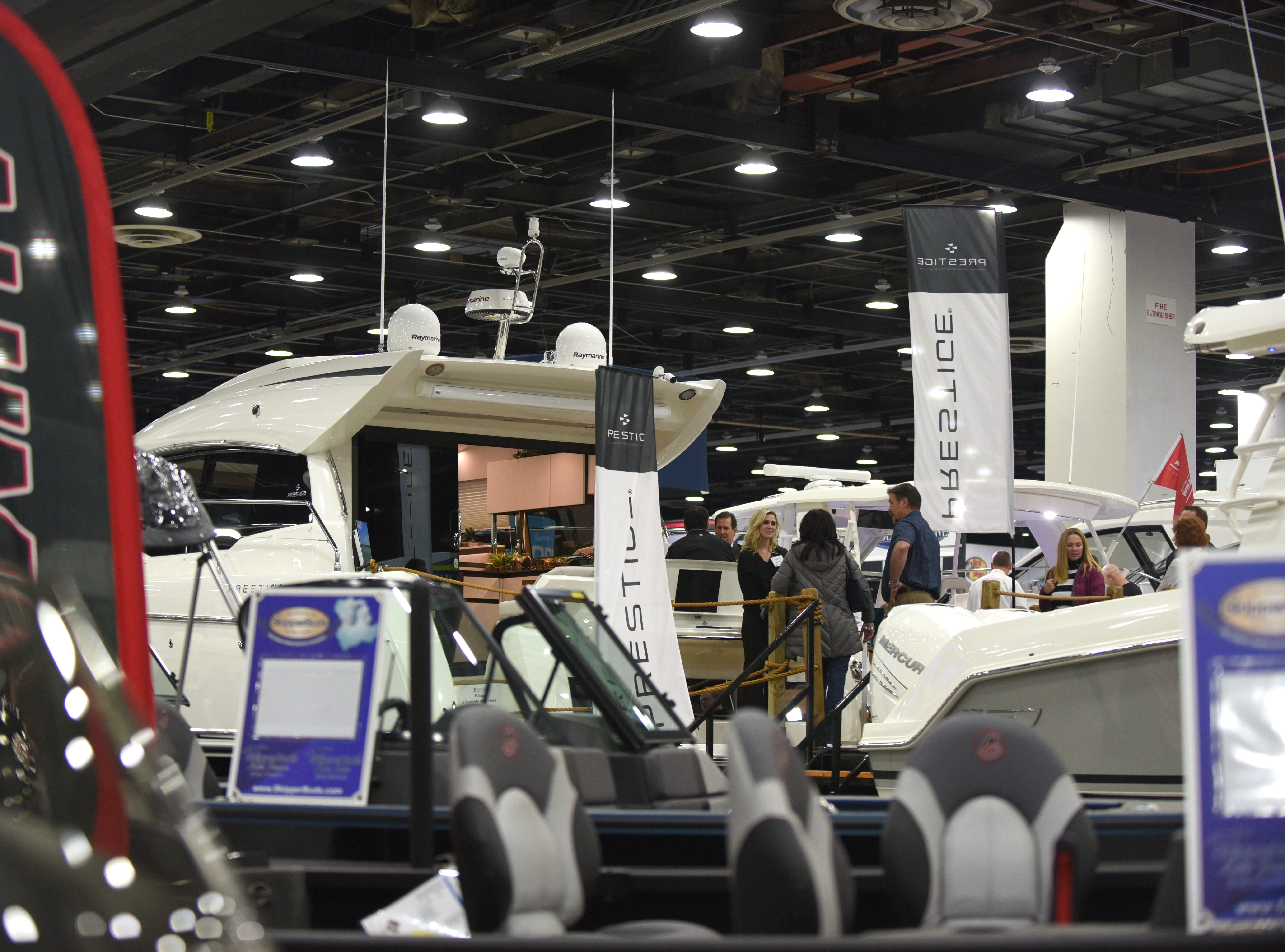 People board pleasure boats on display at the Detroit Boat Show at Cobo Center.