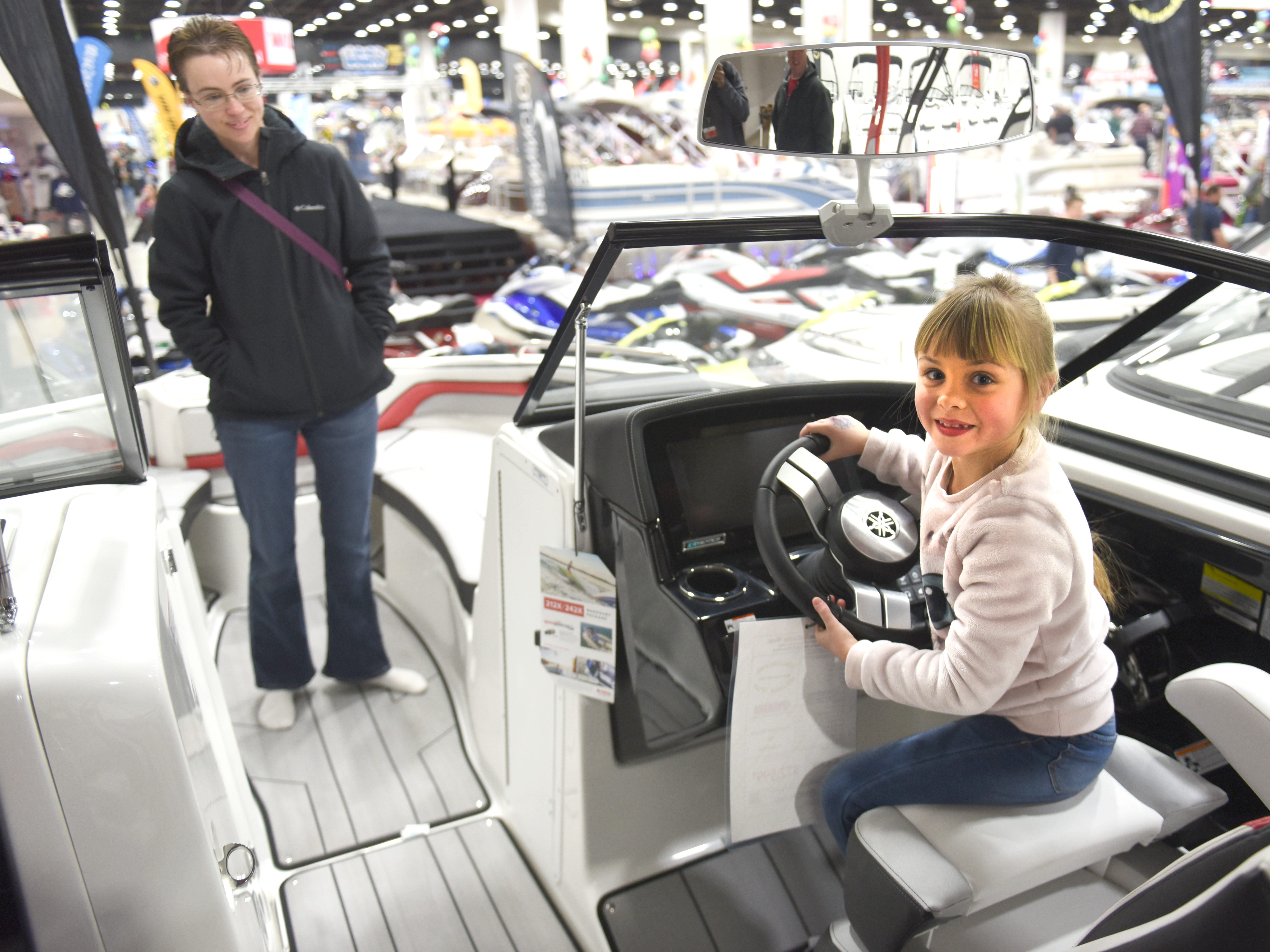 Caylee Young (right), of Monroe, has fun at the wheel of a watercraft from Wonderland Marine West of Howell, as her mother Candy Young watches at the Detroit Boat Show at Cobo Center in Detroit on Saturday.