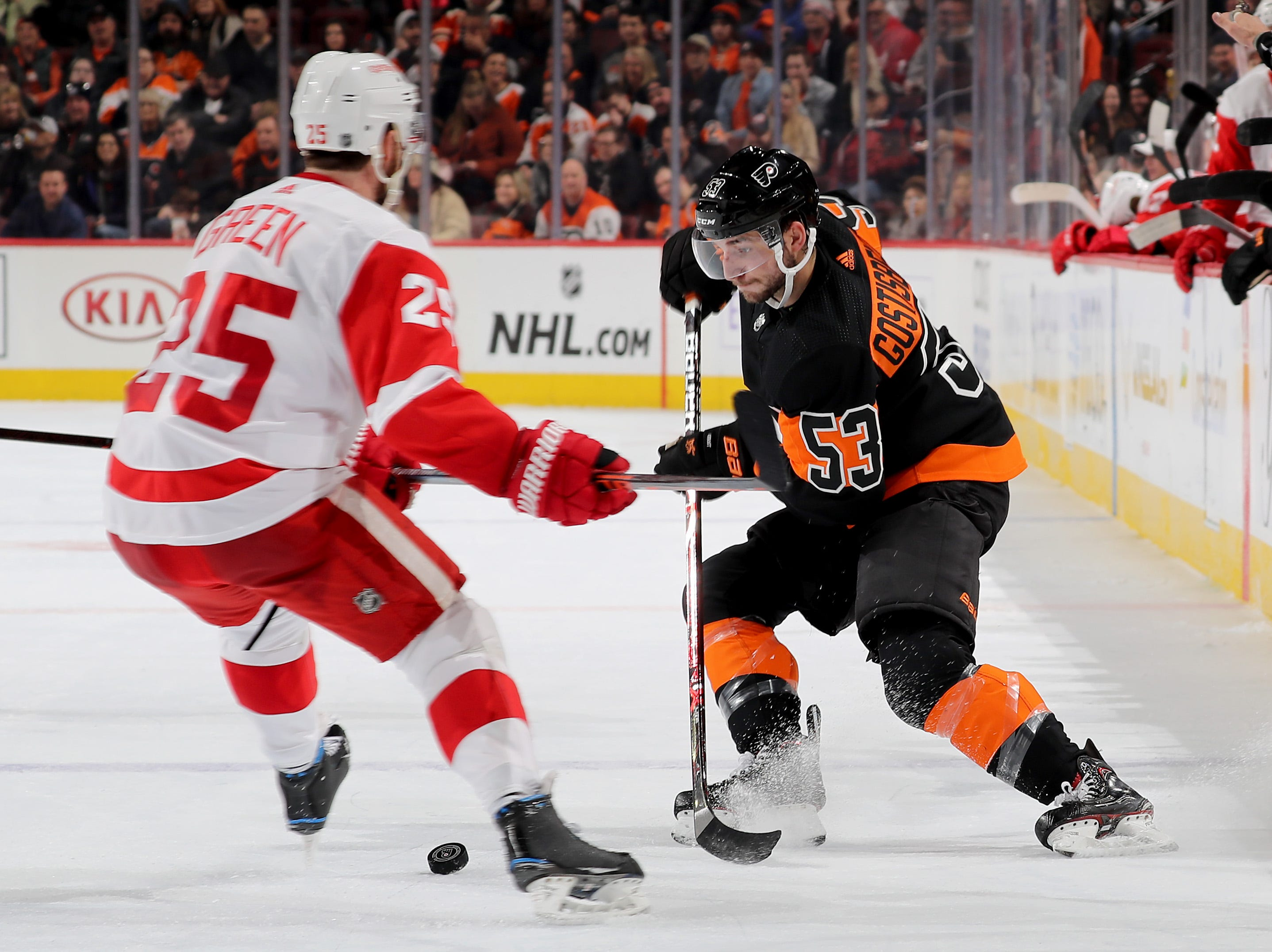 PHILADELPHIA, PENNSYLVANIA - FEBRUARY 16:   Shayne Gostisbehere #53 of the Philadelphia Flyers passes the puck as Mike Green #25 of the Detroit Red Wings defends at Wells Fargo Center on February 16, 2019 in Philadelphia, Pennsylvania. (Photo by Elsa/Getty Images)