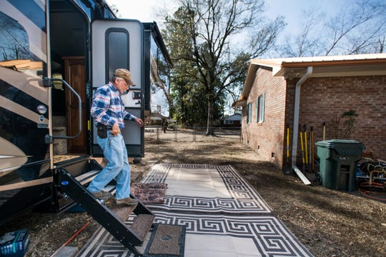 Kevin Tovornik exits his travel camper located in the back yard of his home damaged by flooding from Hurricane Florence near the Crabtree Swamp.