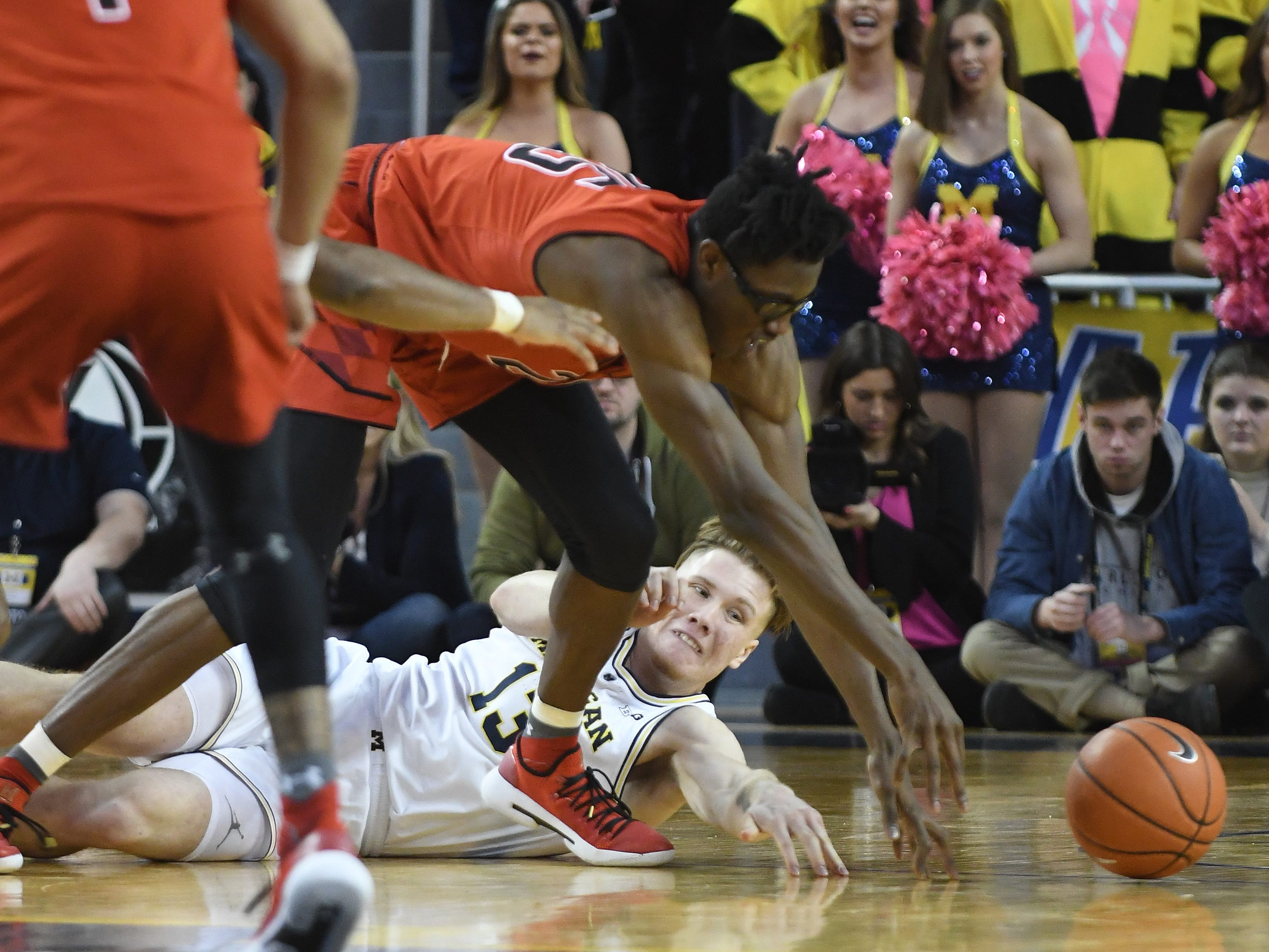 Maryland's Jalen Smith and Michigan's Ignas Brazdeikis hit the floor battling for a loose ball in the second half.