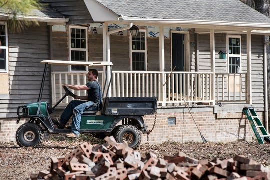 Austin Black works to repair a home damaged by flooding from Hurricane Florence near the Crabtree Swamp.