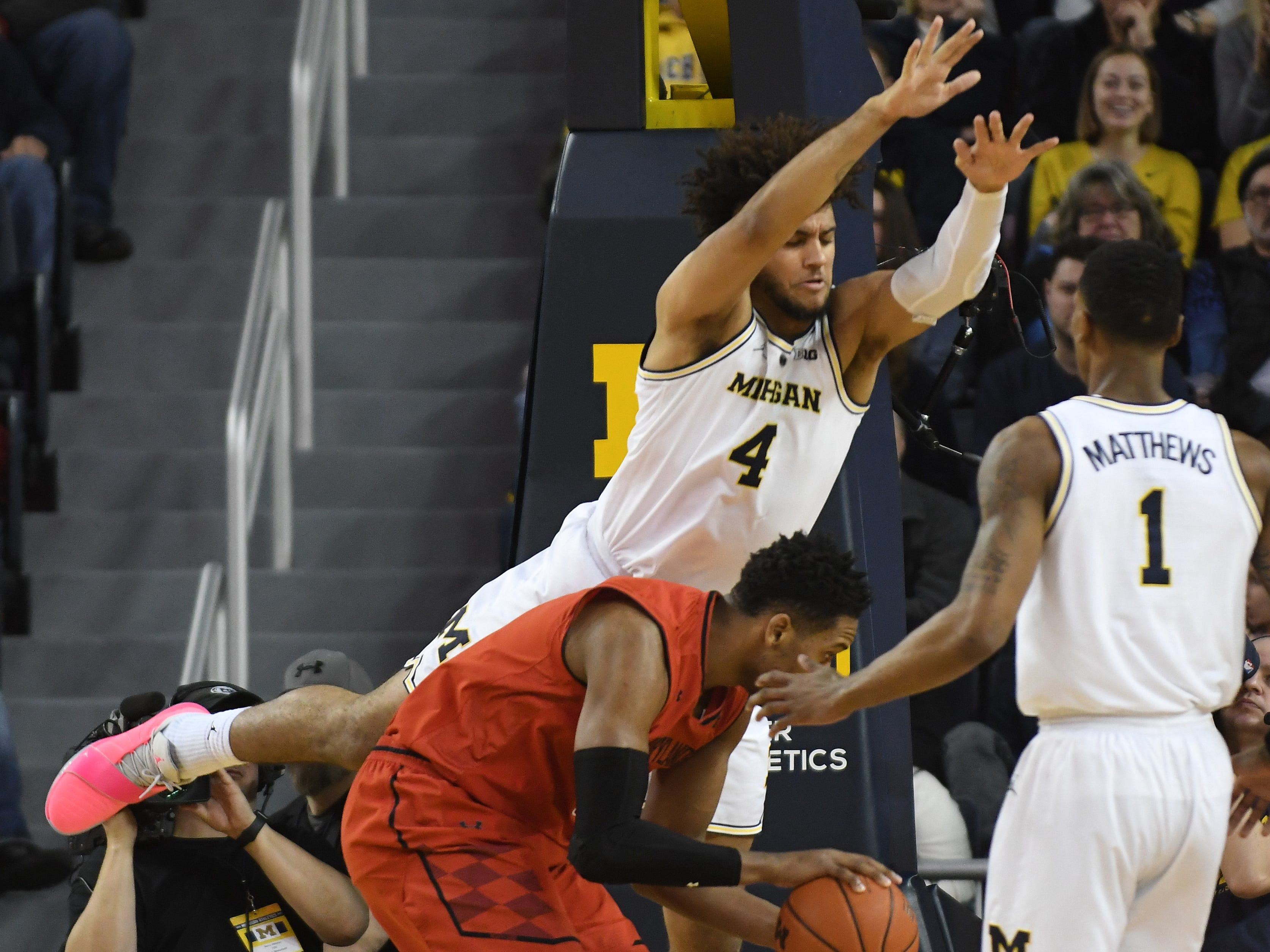 Michigan's Isaiah Livers does his best Superman imitation defending Maryland's Joshua Tomaic in the first half.
