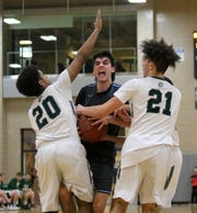 Deegan Sovocool of Moravia battles for possession with Newfield's Arthur Hardison (20) and LaRon Boykin (21) during the IAC Small School boys basketball championship game Feb. 15, 2019 at Tompkins Cortland Community College.