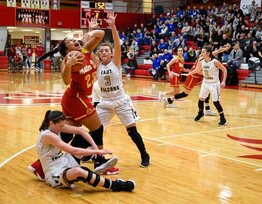 Mater Dei's Mariah Dickerson (23) battles out of a trap as the Evansville Mater Dei Wildcats play the Winchester Community Golden Falcons in the Class 2A Girls Semi-State Tournament at Jeffersonville High School Saturday, February 16, 2019.