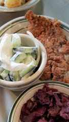 Three Gerst Haus German specialties: wiener schnitzel, cucumber salad with sour cream, and rott trohl red cabbage.