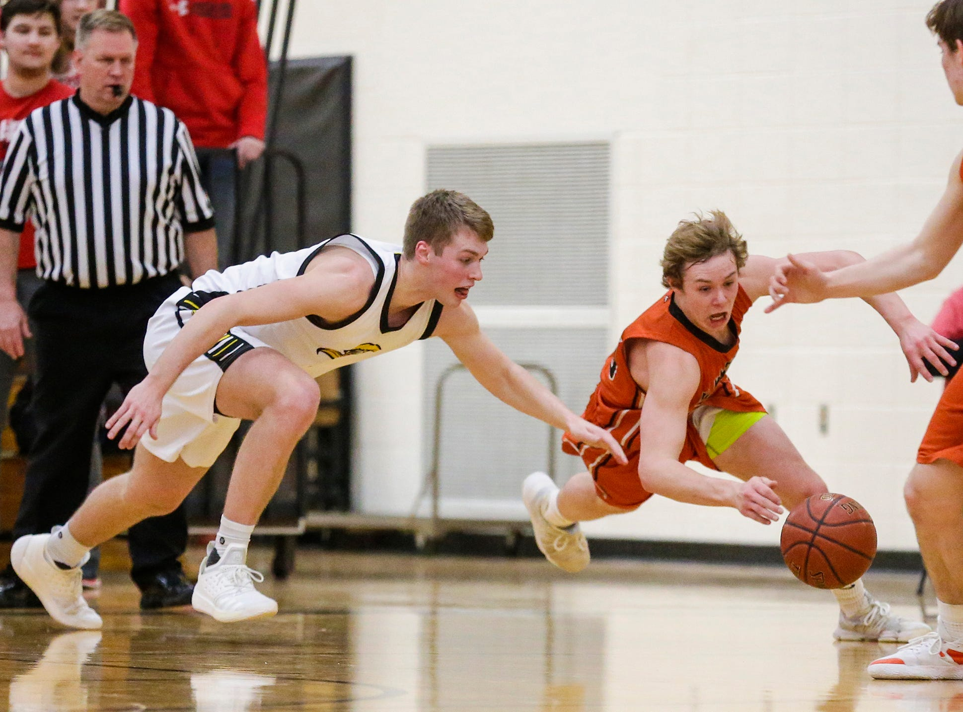 Waupun High School boys basketball's Marcus Domask (1) and Plymouth High School's Aiden Reilly (25) go after a loose ball during their game Friday, February 15, 2019 in Waupun. Doug Raflik/USA TODAY NETWORK-Wisconsin