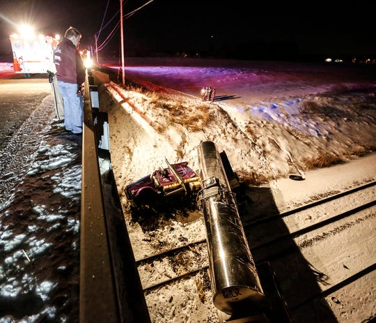 Emergency crews work the scene of a crash Friday, February 15, 2019, where a milk truck crashed over the side of a bridge on Fond du Lac County F between Hickory Road and State 175 and landed on the train tracks below. The driver was taken to a nearby hospital.