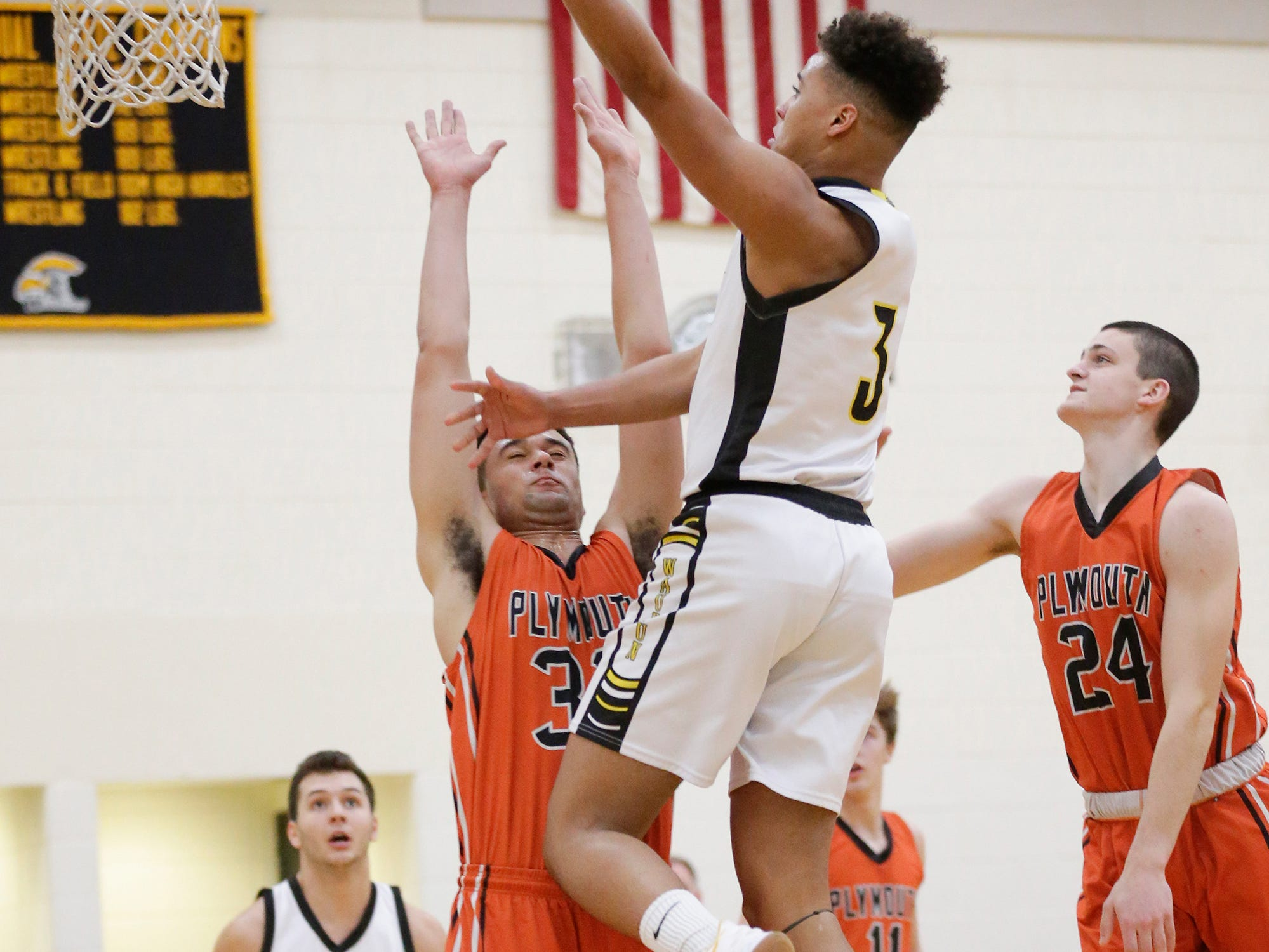 Waupun High School boys basketball's Quintin Winterfeldt goes up for a basket over Plymouth High School's Nick Falls (33) during their game Friday, February 15, 2019 in Waupun. Doug Raflik/USA TODAY NETWORK-Wisconsin