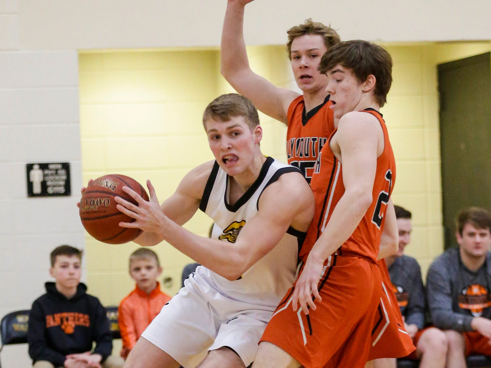 Waupun High School boys basketball's Marcus Domask (1) works his way past Plymouth High School's Aiden Reilly (25) and Cooper Gosse (2) during their game Friday, February 15, 2019 in Waupun. Doug Raflik/USA TODAY NETWORK-Wisconsin