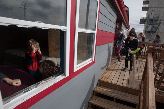 Polaris student Aron Jocobs, right, prepares to storm a house with his teammates while three-year-old Gavin Dembek pretends to be a zombie held up in an interior room with others during a zombie survival simulation on Thursday, Feb. 14, 2019, at the Poudre Fire Authority tarring facility in Fort Collins, Colo. In this simulation the team entering the house is tasked with collecting supplies scattered around the home while avoiding the zombie horde inside and around the house.