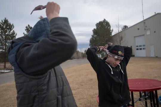 Polaris students Adam Workman, left, and Aron Jocobs put on bandanas marking them as zombies before participating in a zombie survival simulation on Thursday, Feb. 14, 2019, at the Poudre Fire Authority tarring facility in Fort Collins, Colo.