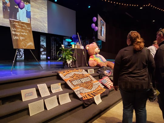 Attendees look at items placed in the front of the Foundations Church auditorium for the celebration of life for William Jason Wheeler, the man who died in a Loveland road rage incident Feb. 8.