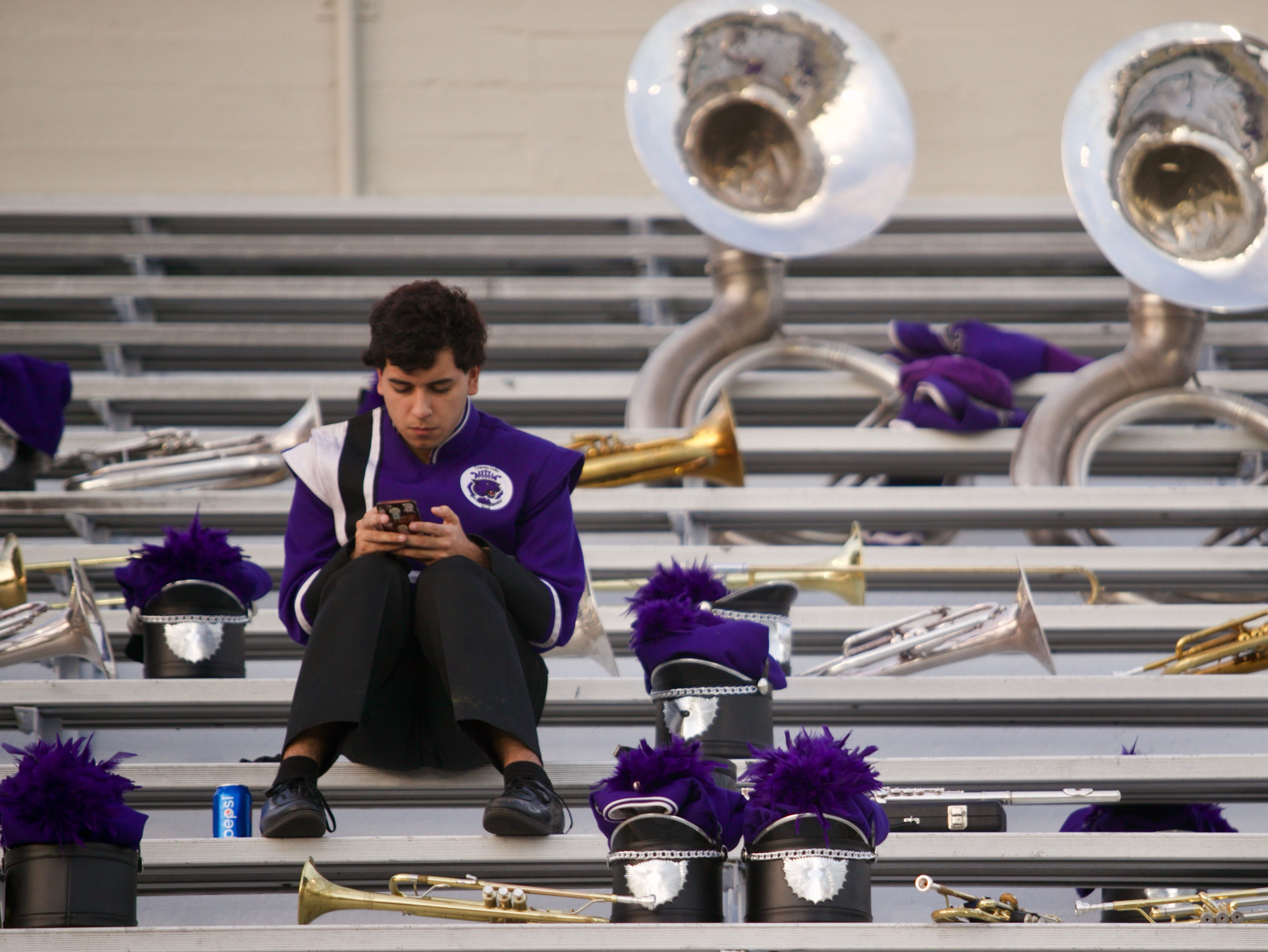 A band member waits at Fort Myers High School Stadium for the start of the parade.