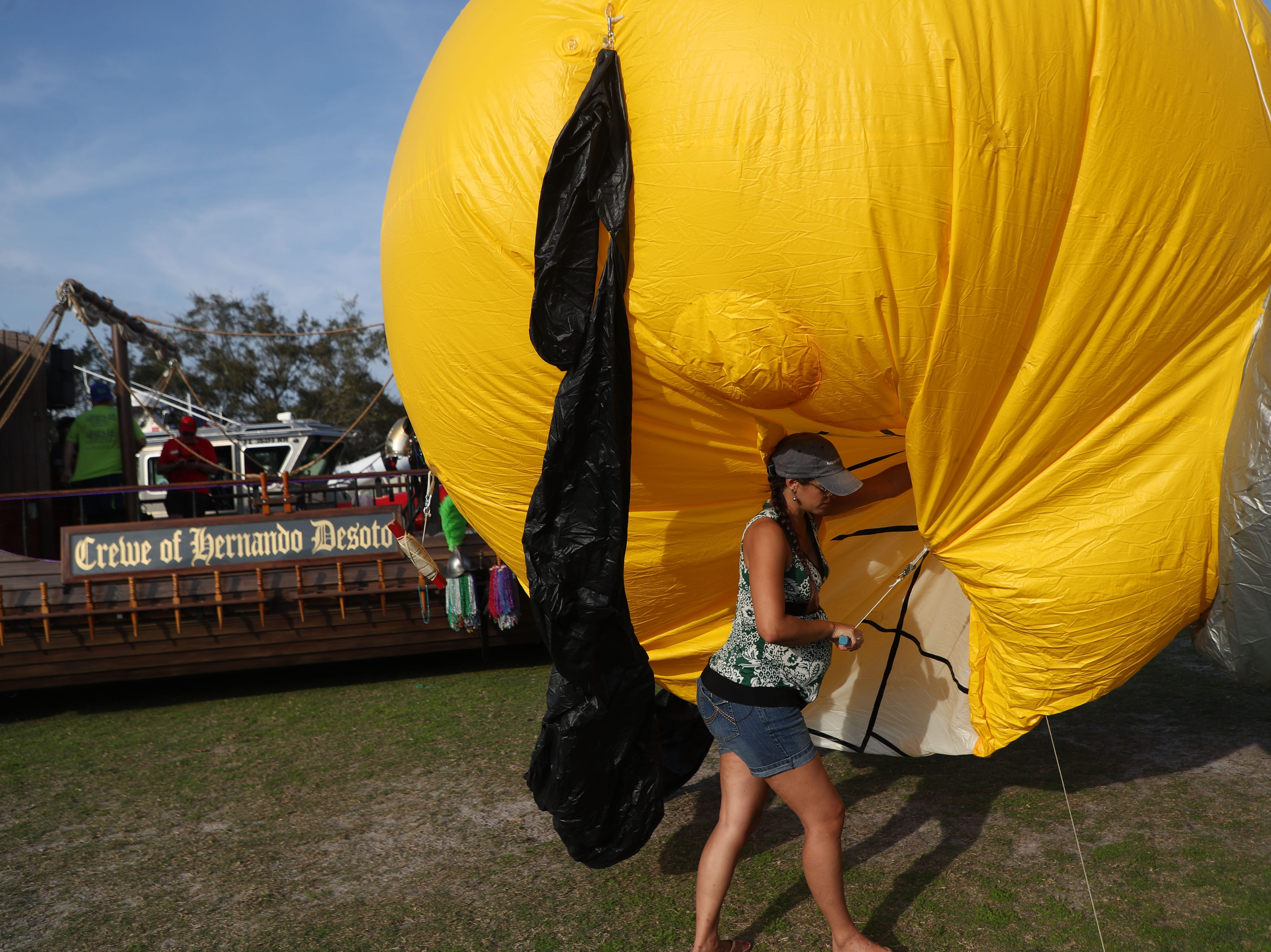 Rynelle McKim helps set up the LCEC balloon before the start of the Edison Festival of Light Grand Parade at Fort Myers High School on Saturday 2/16/2019.