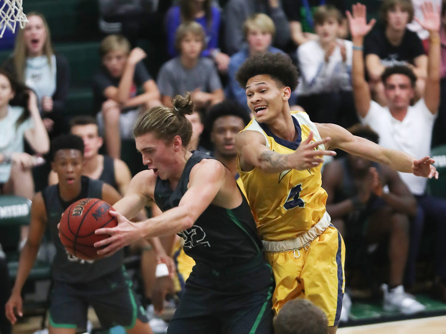 Fort Myers High School's Michael Roberts, left, rebounds against Lehigh on Friday in the Class 7A-11 championship game in Fort Myers. Fort Myers beat Lehigh 59-56.