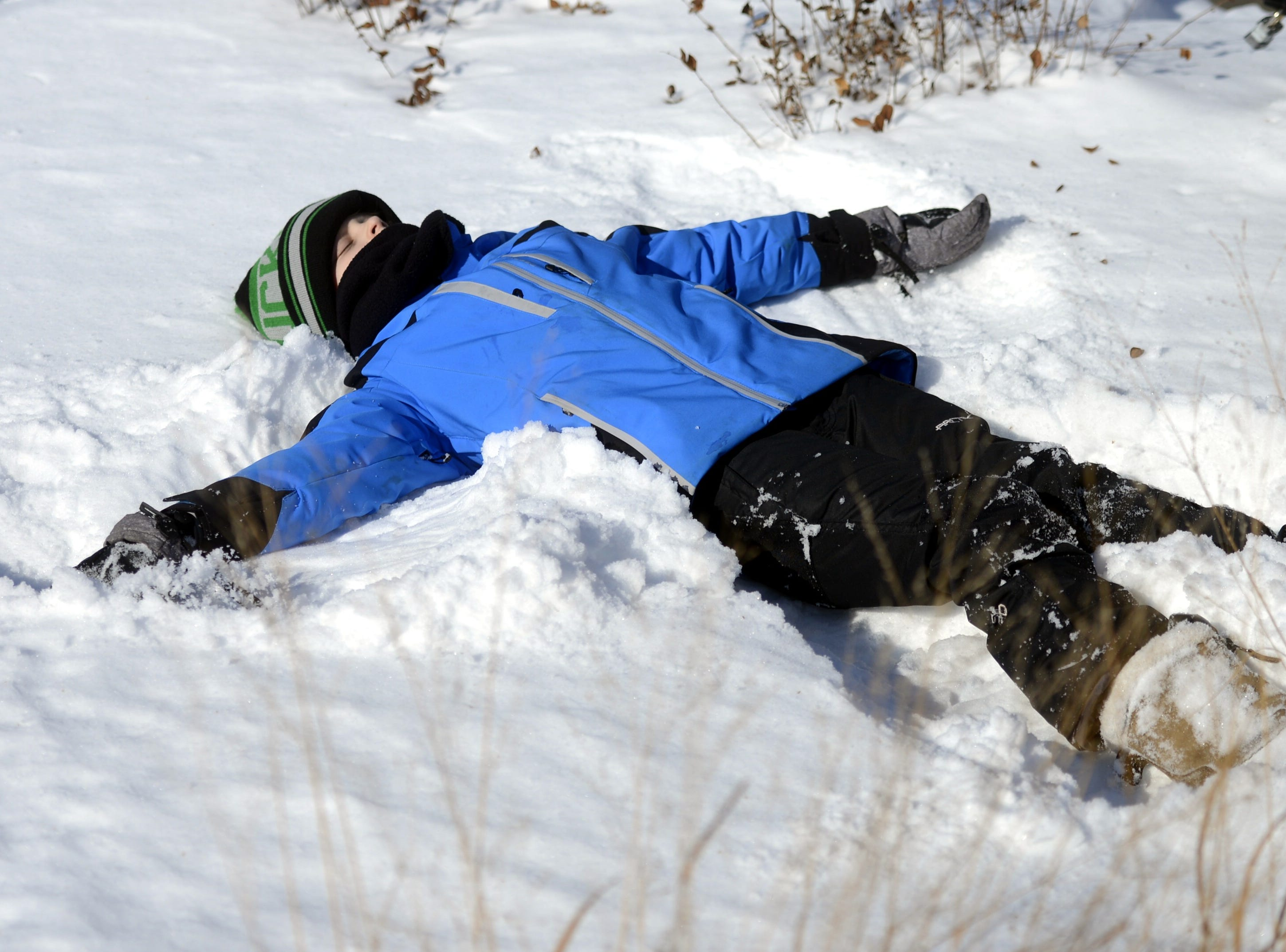 Carter Nitke, 10, of Green Bay makes a snow angel at the Titletown Winter Games on Saturday, Feb. 16, 2019.