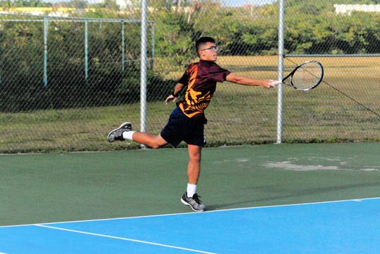 A Father Duenas doubles player returns a serve against Harvest Christian Academy in the match between FD's Kane Dawson/Aaron Gumataotao vs. Harvest's Daniel Lee and Abraham Kim.