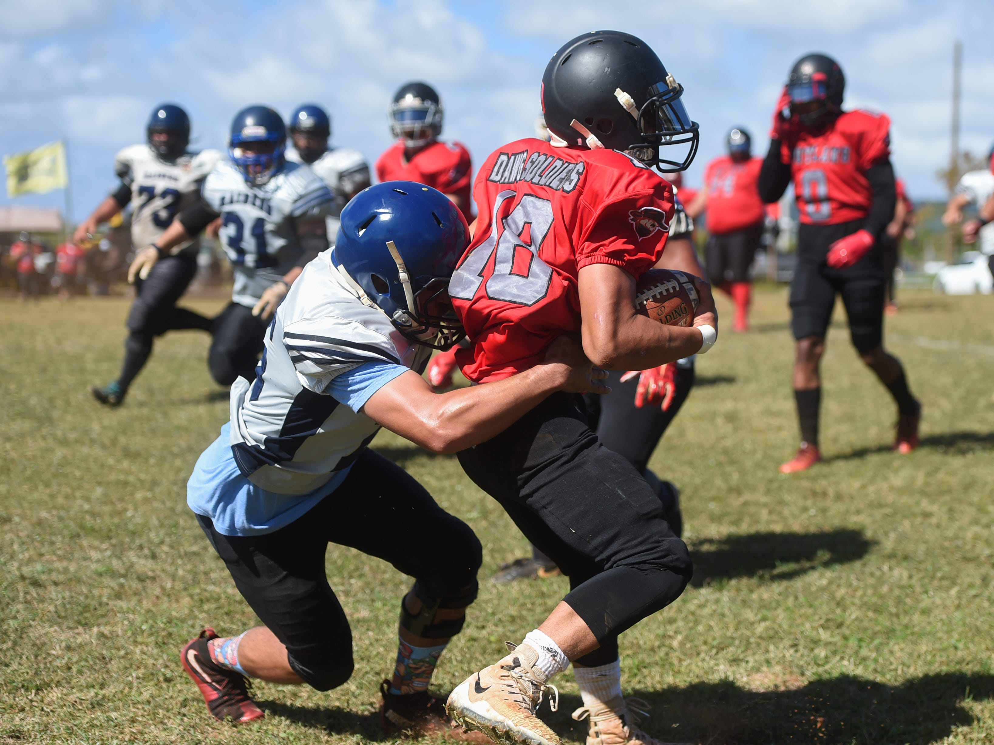 Outlaws player Justin Tanguileg (18) is tackled by a Guam Raiders player during their Budweiser Guahan Varsity Football League game at Eagles Field in Mangilao, Feb. 16, 2019.