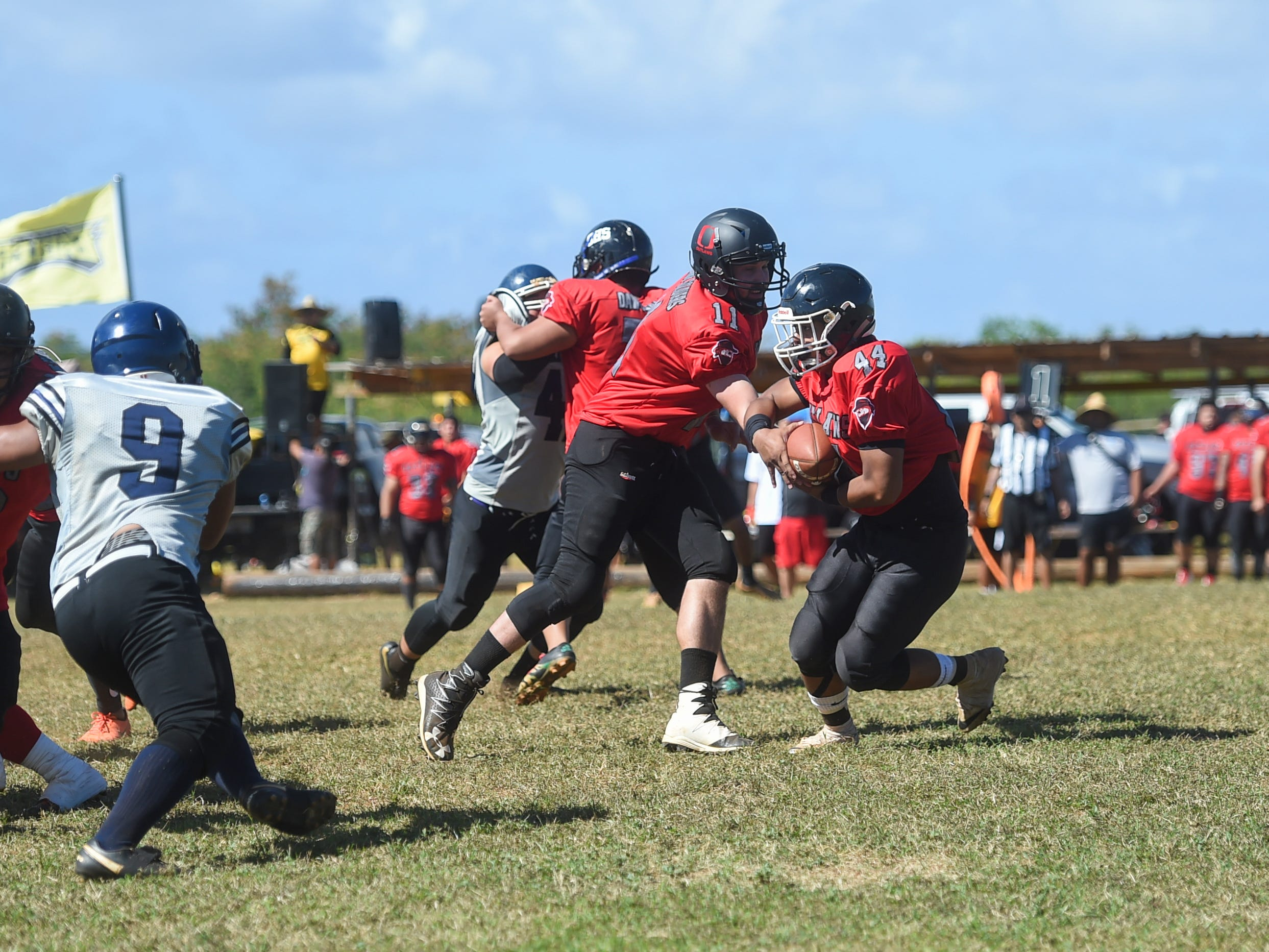 Outlaws quarterback Victor Malveaux (11) hands the ball off to teammate Kobe Quimbao (44) during their Budweiser Guahan Varsity Football League game against the Guam Raiders at Eagles Field in Mangilao, Feb. 16, 2019.