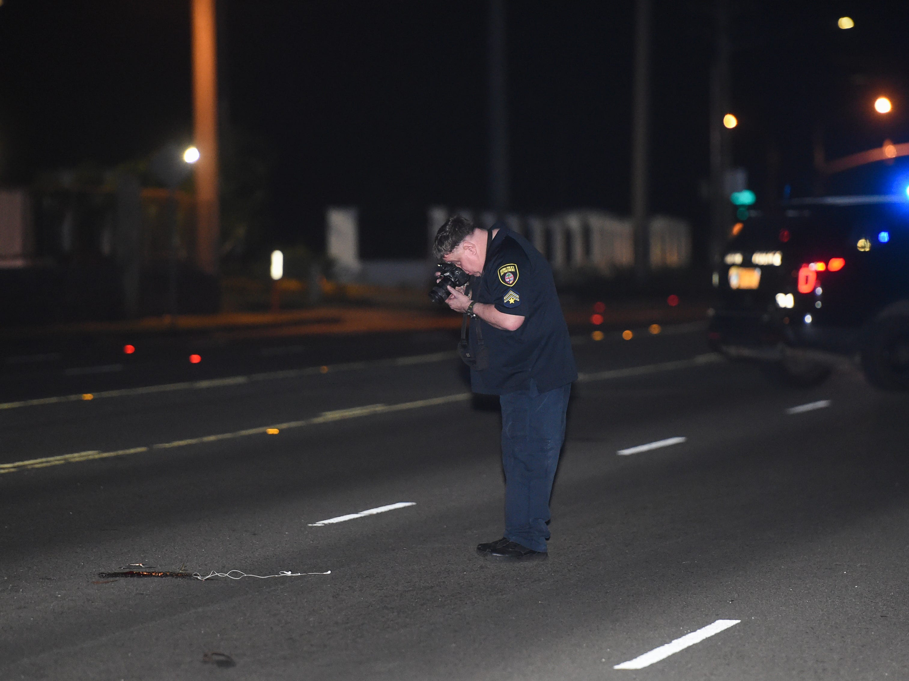 Guam Police Department officer Bob Travis takes photos at the scene of an auto-pedestrian crash across Coast 360 Federal Credit Union on Route 8 in Maite, Feb. 17, 2019.