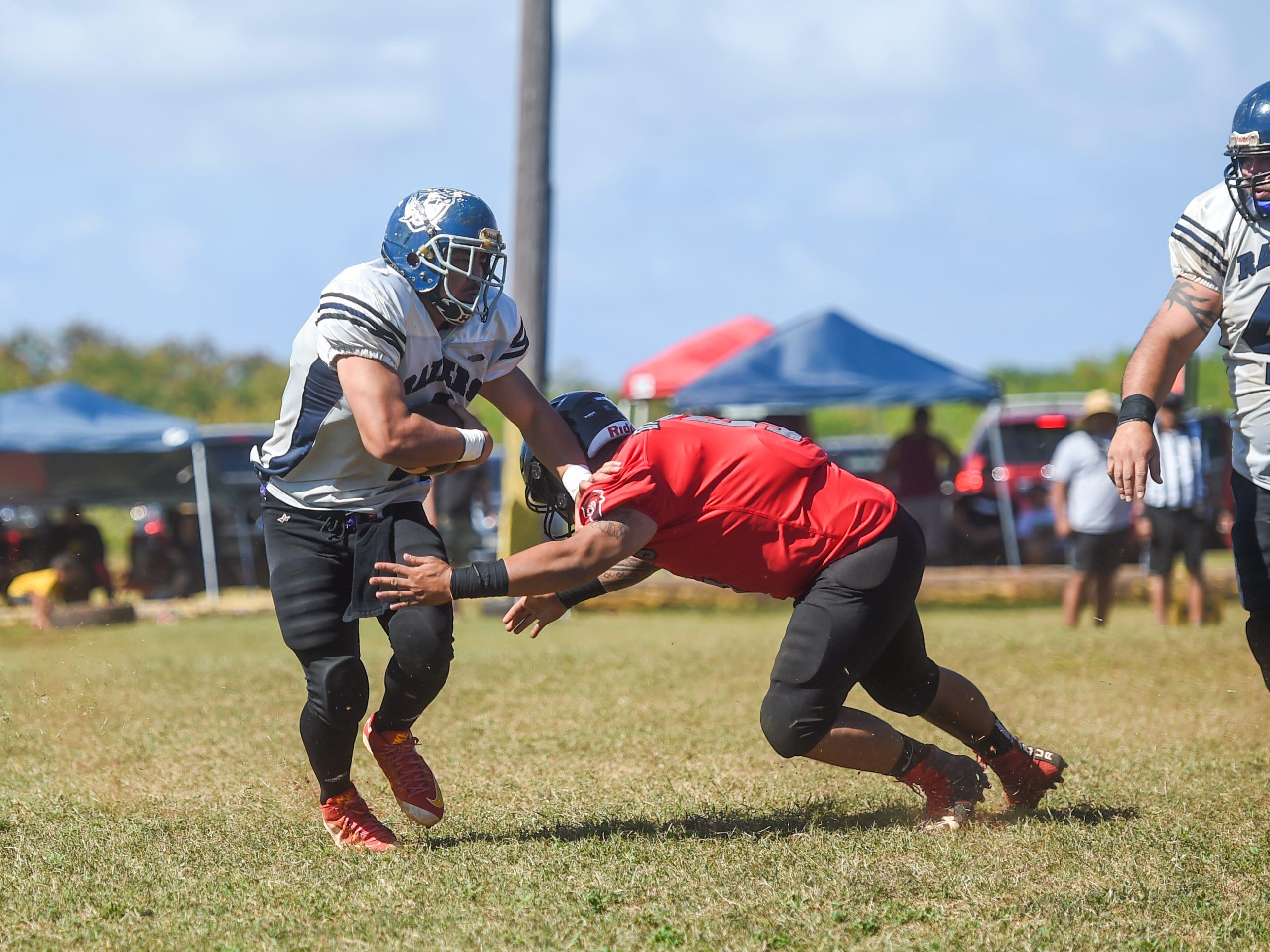 Guam Raiders player Kellen Kawasaki runs the ball against the Outlaws during their Budweiser Guahan Varsity Football League game at Eagles Field in Mangilao, Feb. 16, 2019.