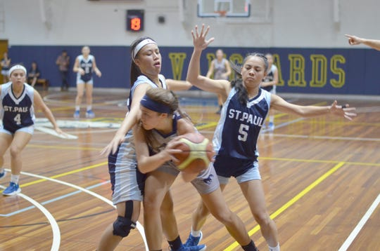 The Warriors' Johnia Siguenza, left, and Isla Quinata smother an opponent from the Morrison Academy Mustangs. The Warriors beat the Mustangs 53-41 at the 2019 Asian Christian Schools' Conference Girls' Basketball Tournament in Manila.